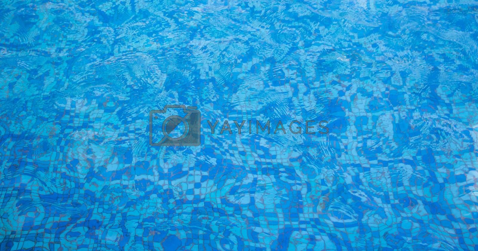 A pool with a mosaic bottom. Blue transparent water ripples. Space for text