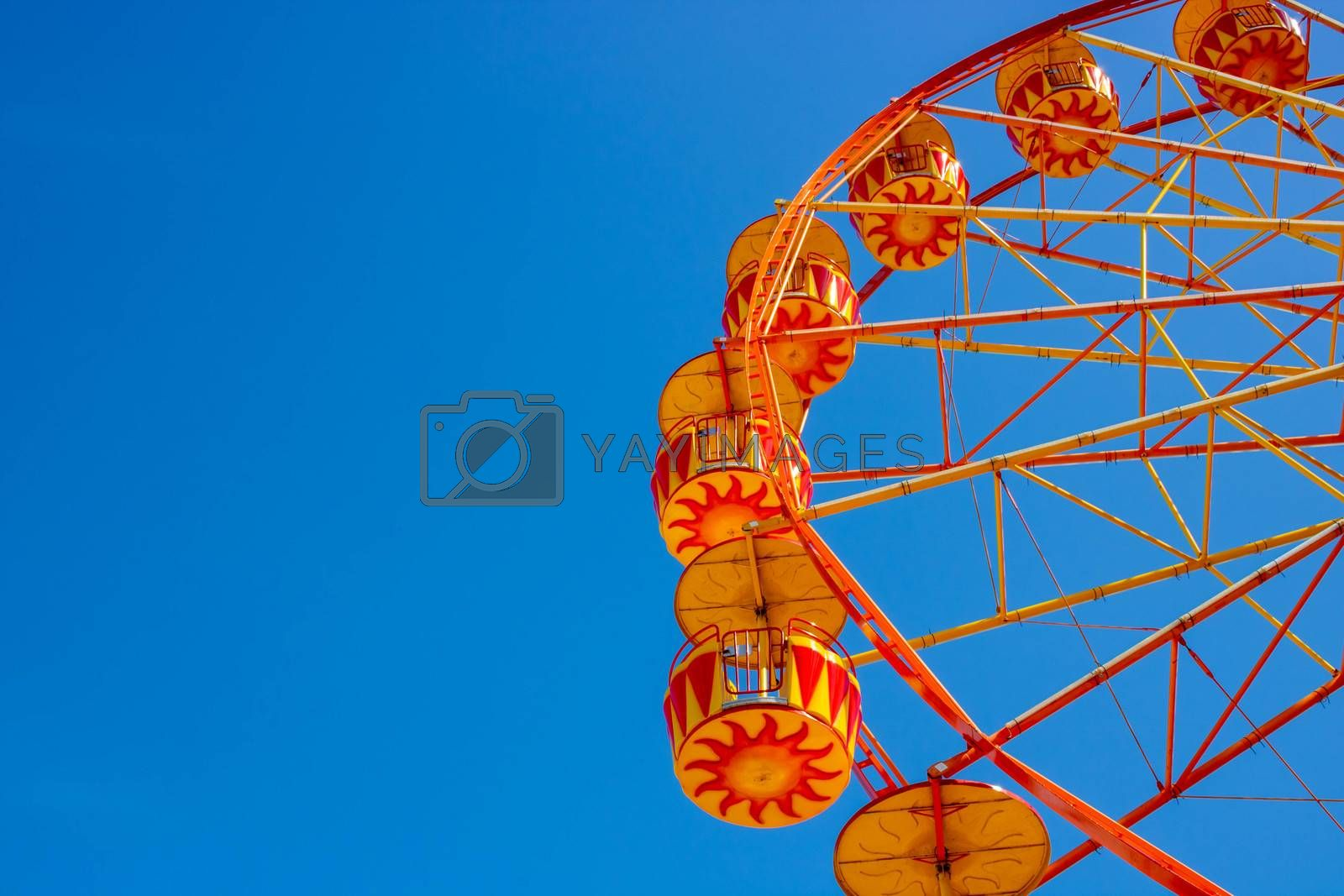 Yellow Ferris Wheel against a blue sky. Space for your text