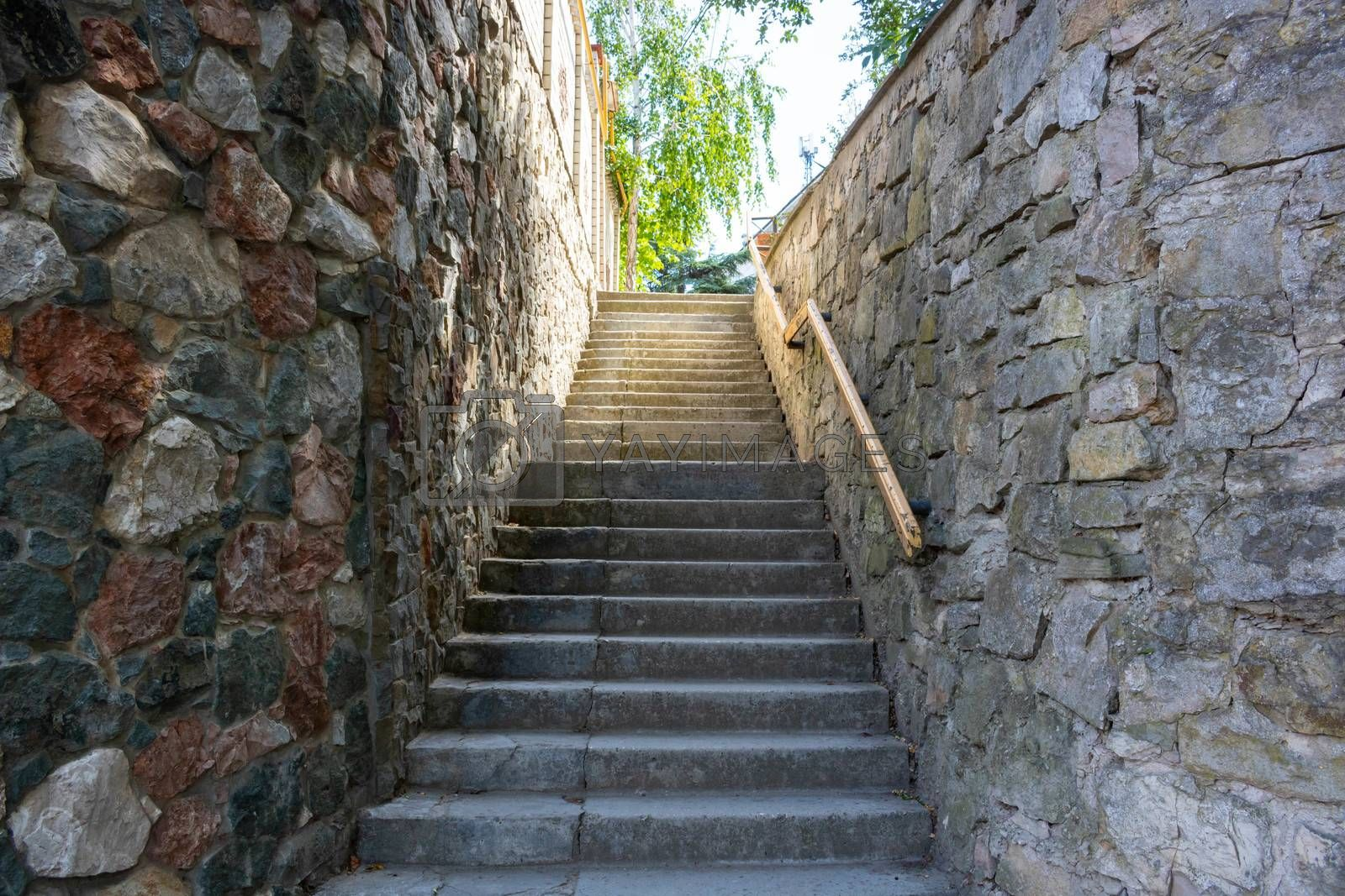 A stone staircase with a railing leading up.Summer day.