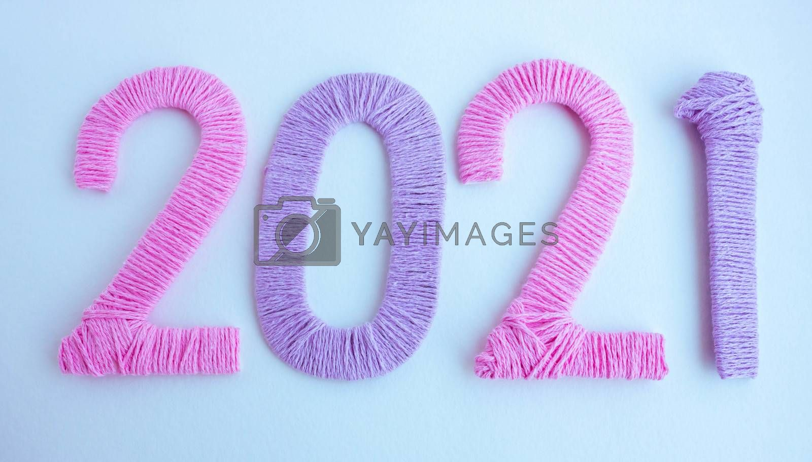 The numbers 2021 are made of pink and lilac threads on a white background. The concept of a New year.