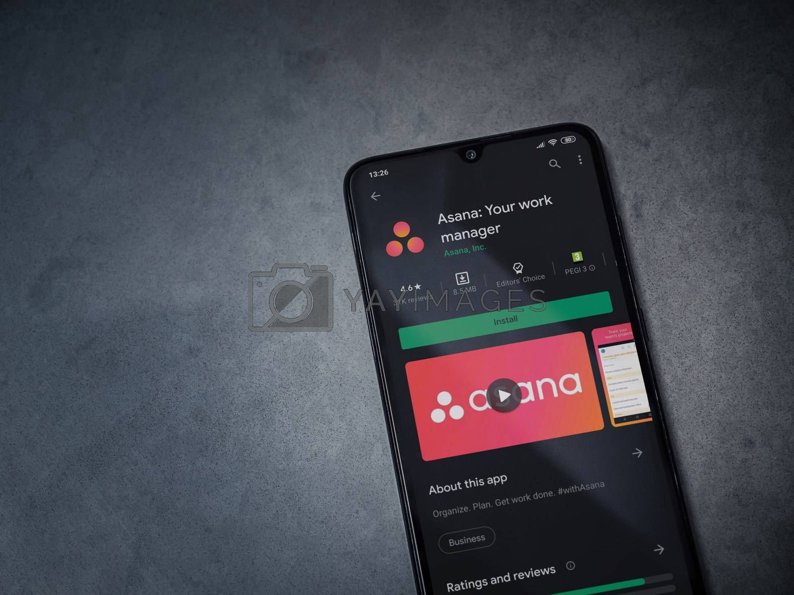 Lod, Israel - July 8, 2020: Asana app play store page on the display of a black mobile smartphone on dark marble stone background. Top view flat lay with copy space.