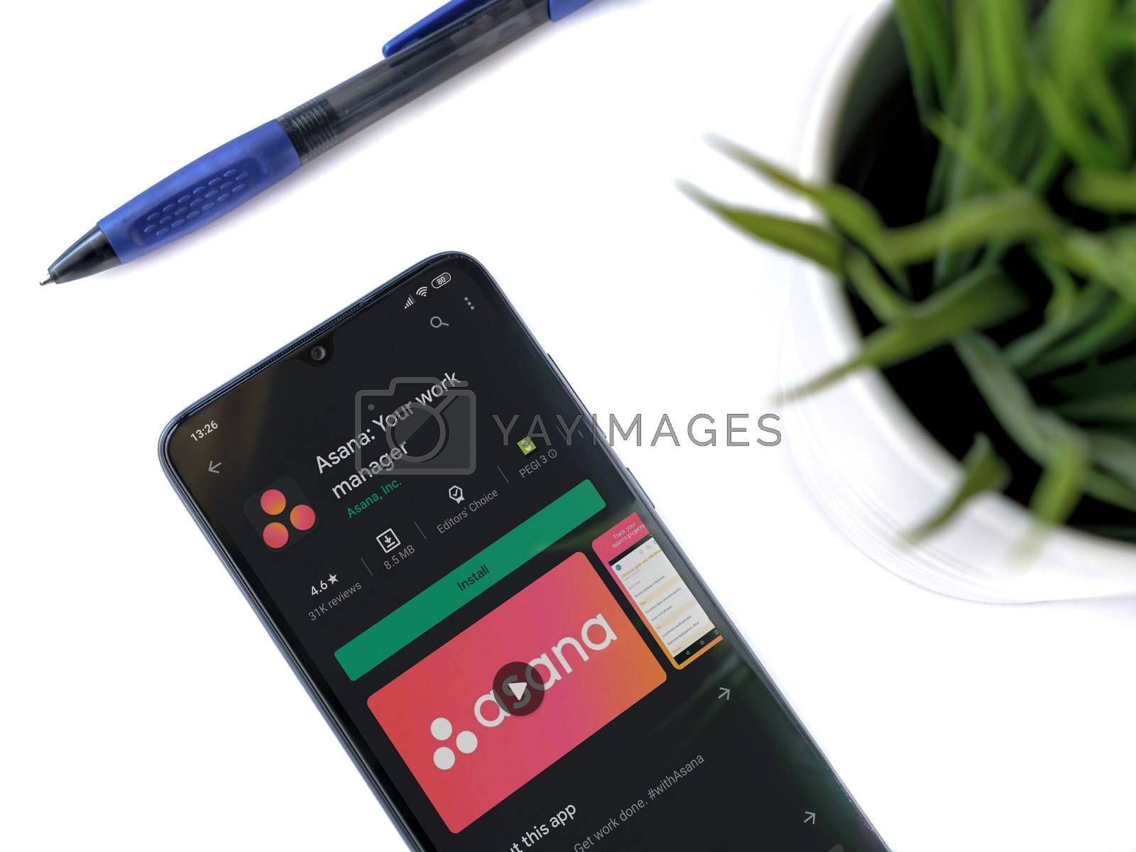 Lod, Israel - July 8, 2020: Modern minimalist office workspace with black mobile smartphone with Asana app play store page on white background. Top view flat lay with copy space.