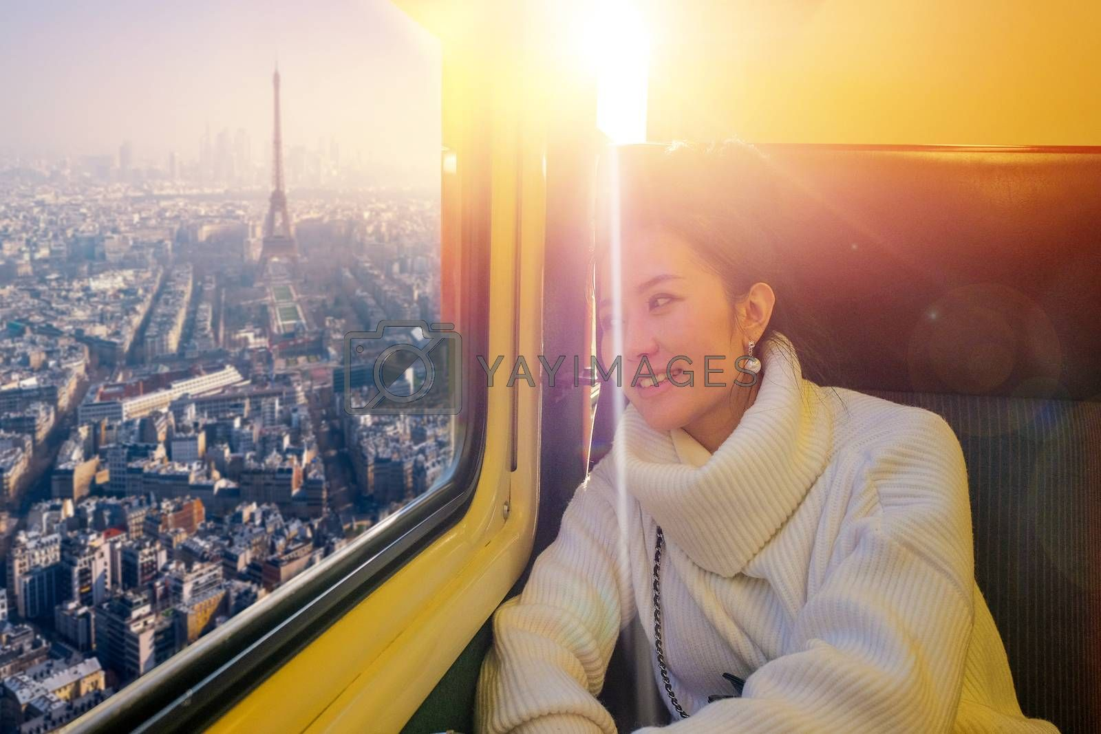 Young beautiful woman traveling looking view Eiffel in sunset while sitting in the train at paris, France
