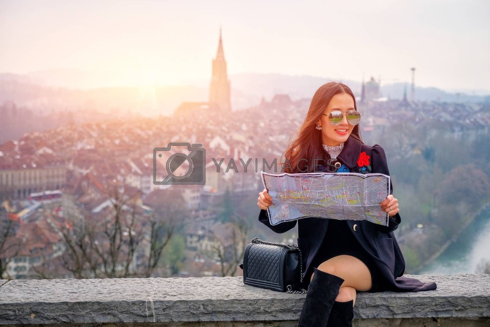 Young female tourist with map looking for a way to Beautiful view point near old town in Bern, Switzerland