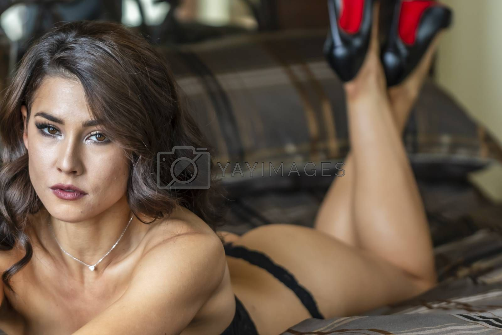 A gorgeous brunette model poses in lingerie in a bedroom environment
