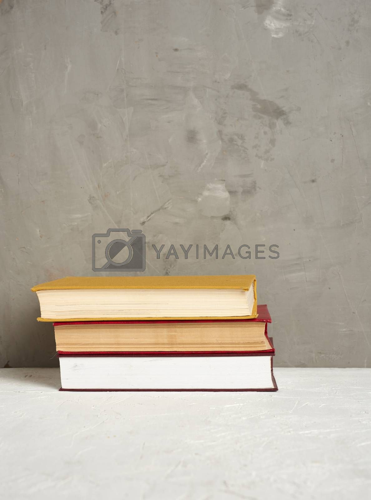 stack of various hardback books on a gray background, place for text, back to school