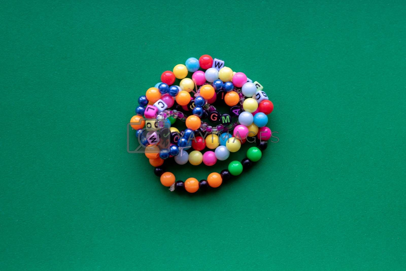 Eight multi-colored bracelets arranged in a flower shape on a green background. Bracelet with beads.