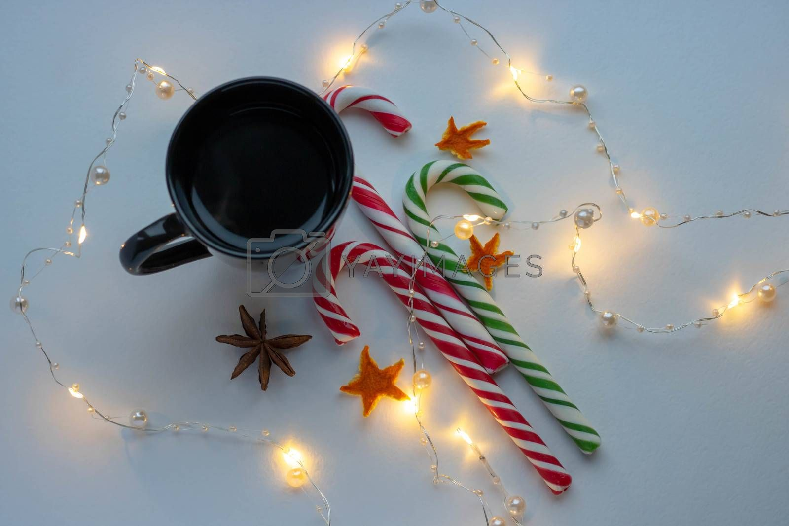 Christmas and winter concept. Black cup of hot coffee, candy cane and garland of white background.Top view. Holiday breakfast.