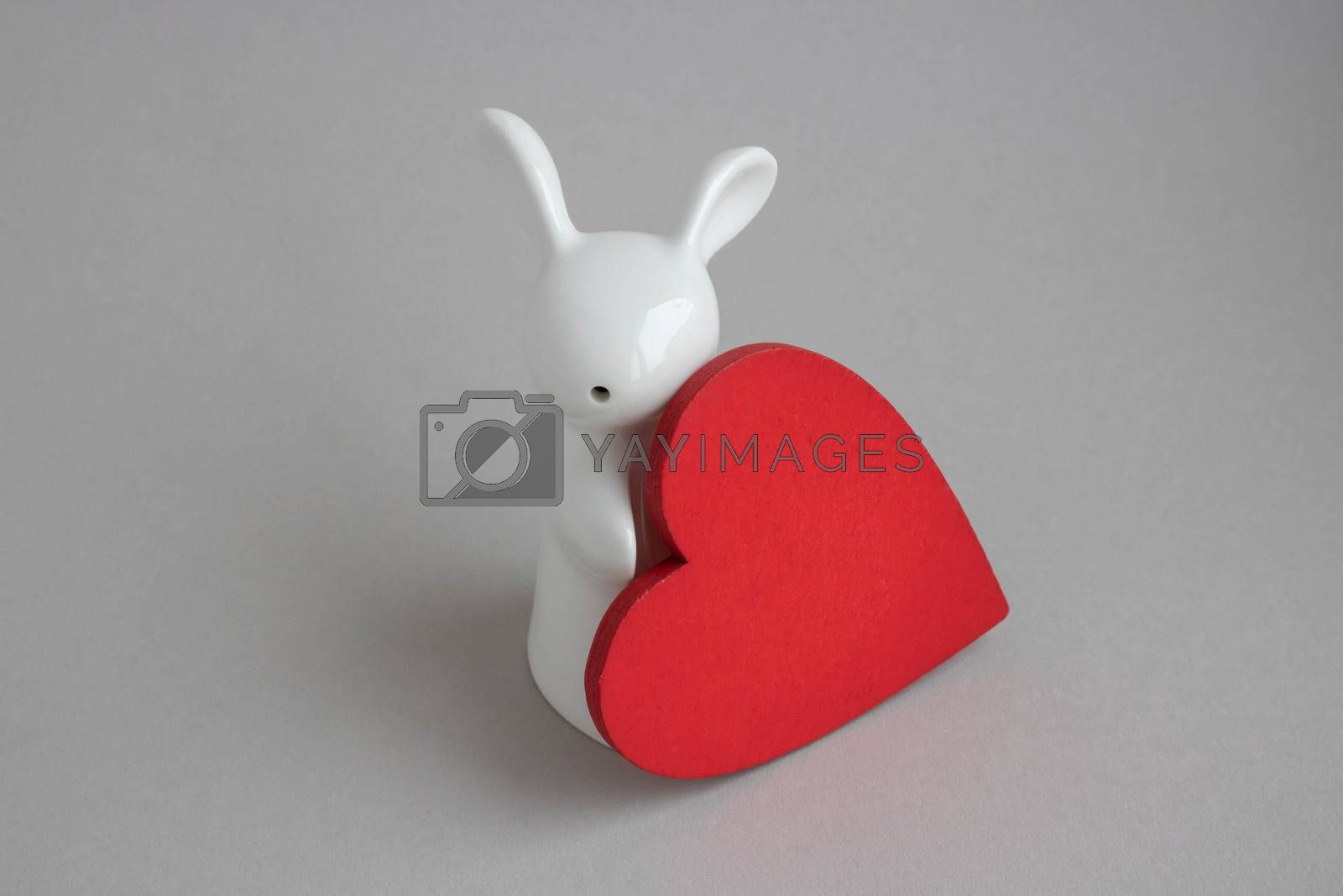 Beautiful ceramic rabbit on white background. statuette of a white rabbit with a red heart.Easter decor