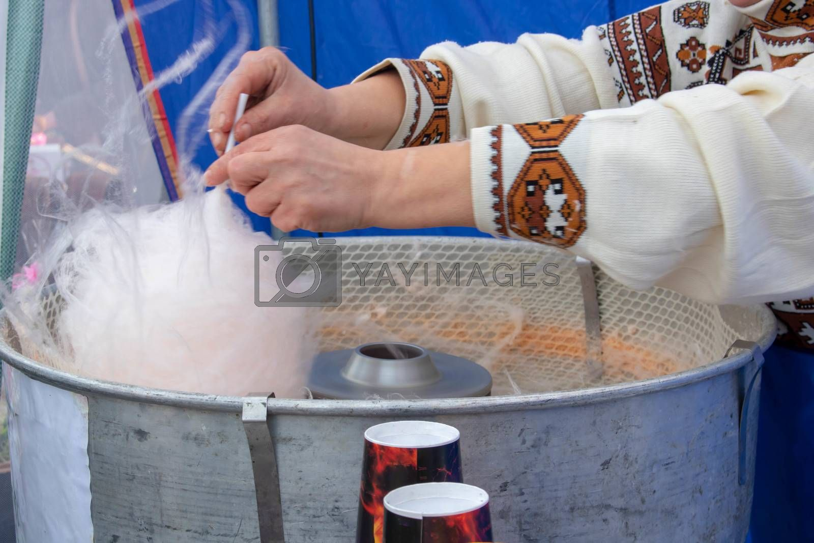 A person in latex gloves making pink cotton candy on a stick