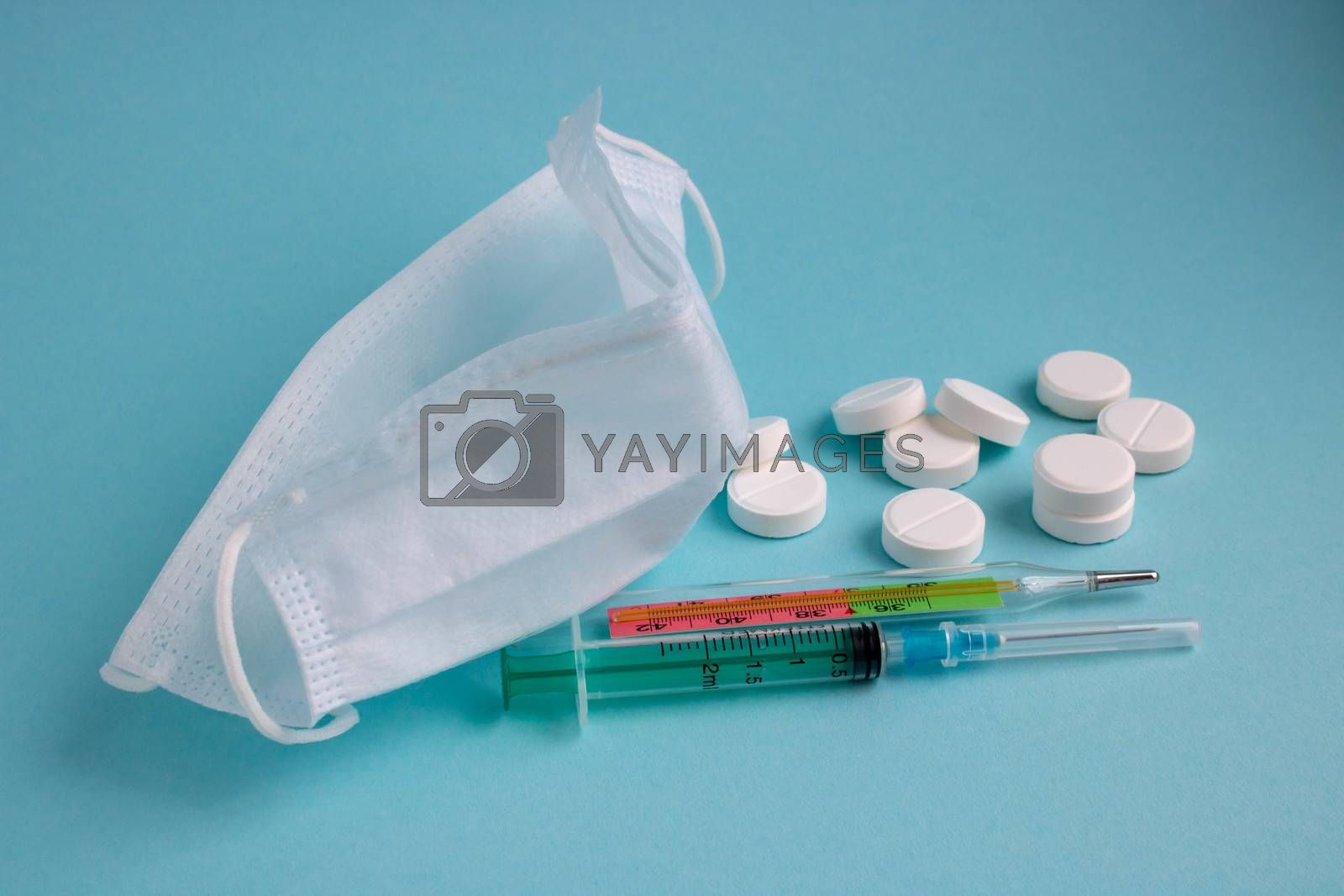 anti-virus medical supplies. concept of deadly coronavirus epidemic. thermometer, mask, syringe with vaccine and antibiotic pills
