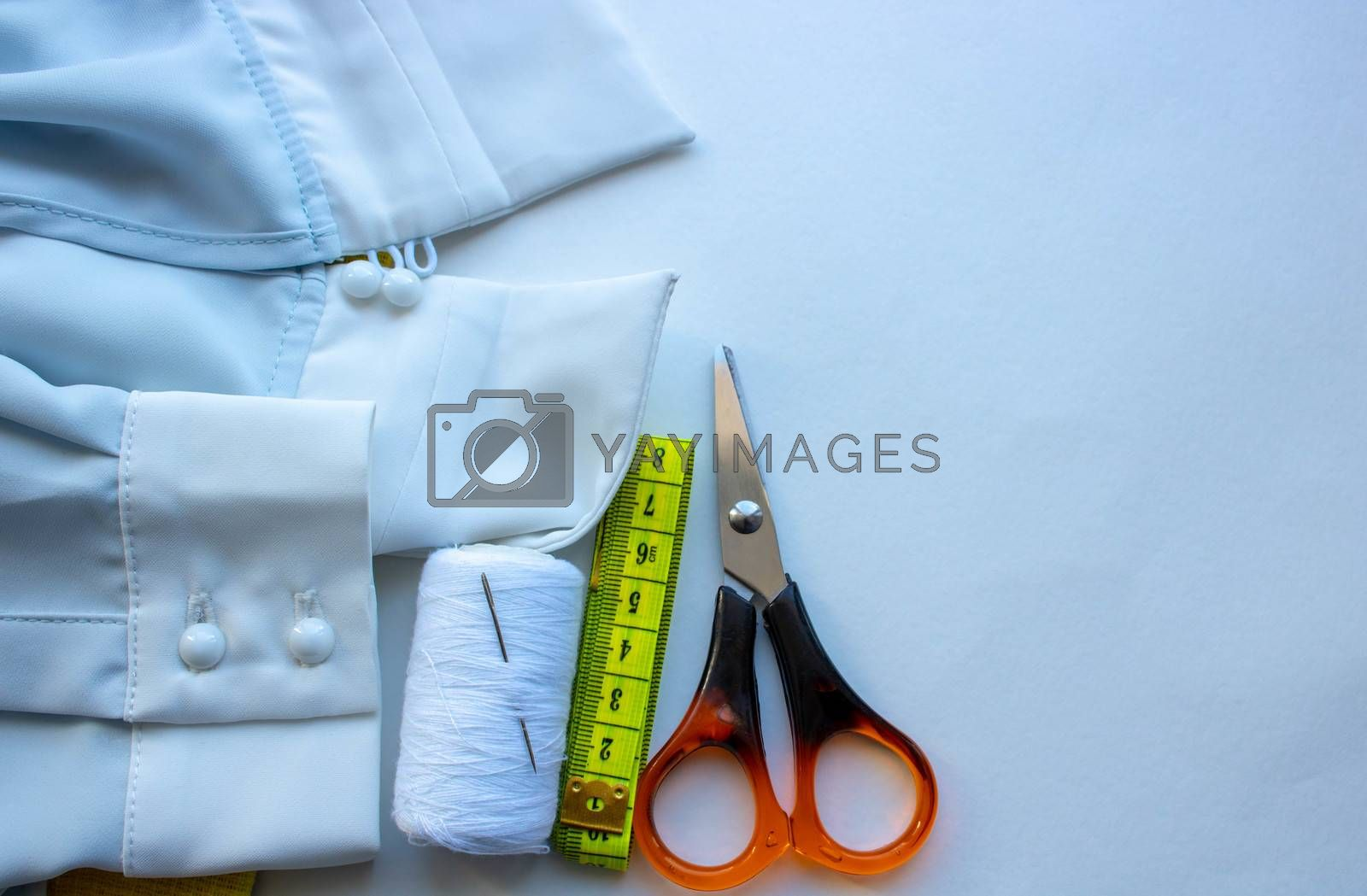 fabric for sewing clothes. Items for sewing clothes. Centimeter tape, tailoring scissors, thread, zipper and blue fabric for sewing clothes.