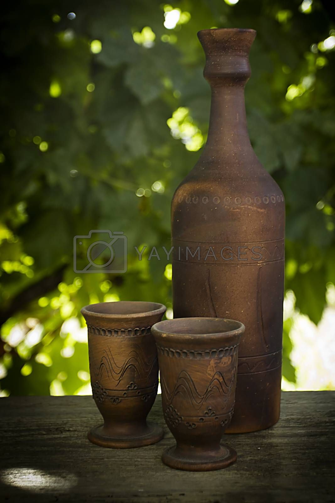 Wine in a clay bottle and glasses outdoors