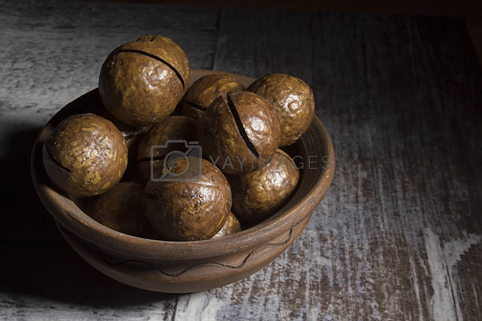 Macadamia nuts in shells in earthenware dish on wooden table