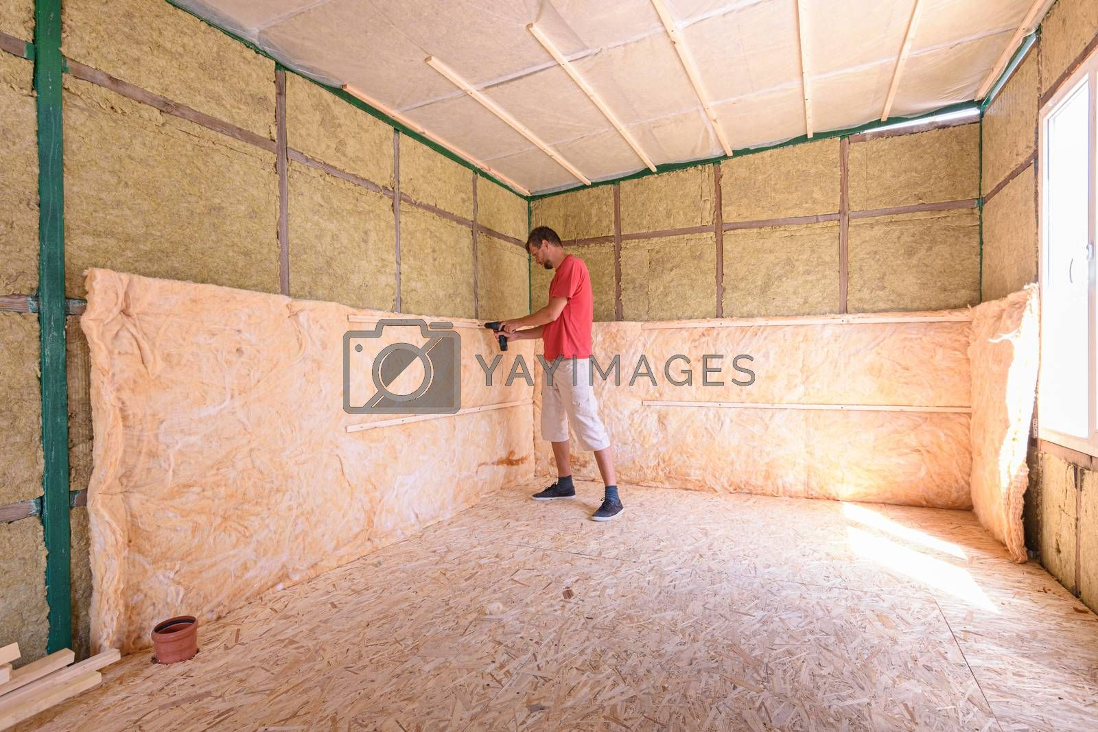 A worker is installing a roll of insulation in the construction of a country house