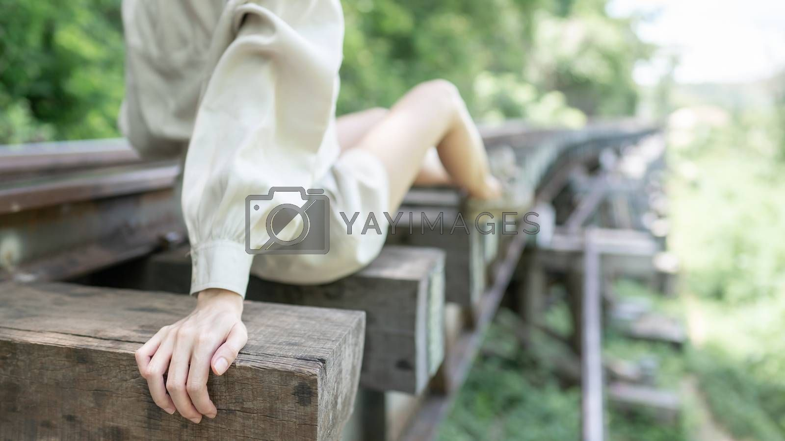Close up of woman sitting on vintage railroad, railway tracks in a rural scene.