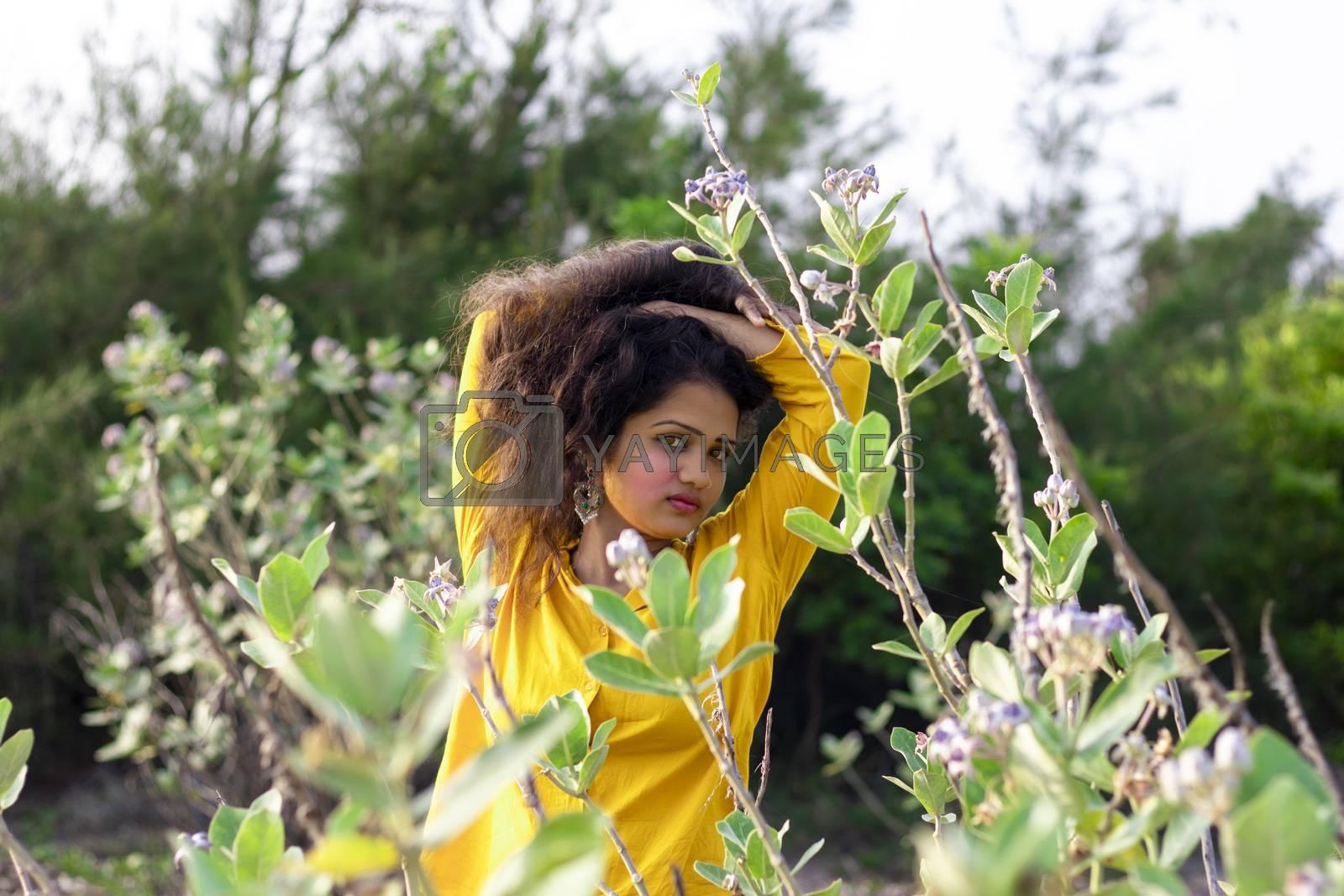 A pretty Asian female model standing near the Aak, Madar (Calotropis gigantea) tree wearing a yellow top , beautiful looking at camera