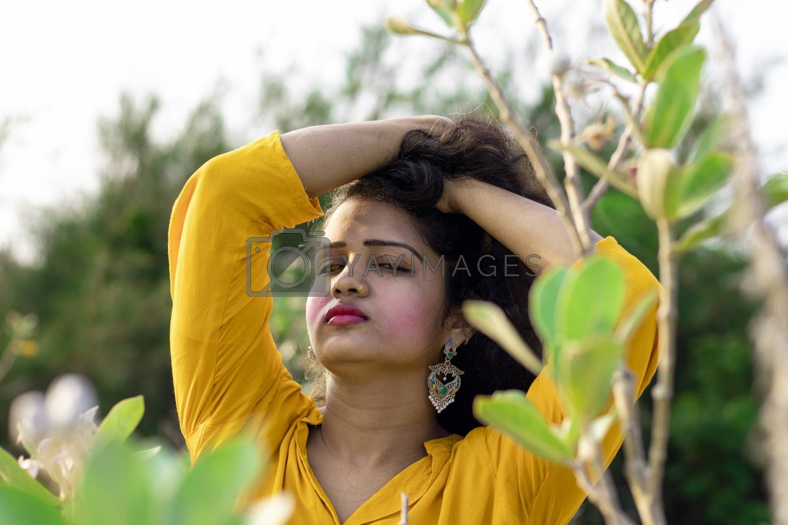 A beautiful Asian woman is standing near the tree of Aak, Madar (Calotropis gigantea) wearing a yellow top and holding black and long hair in her hands, elective focus points background,outdoors