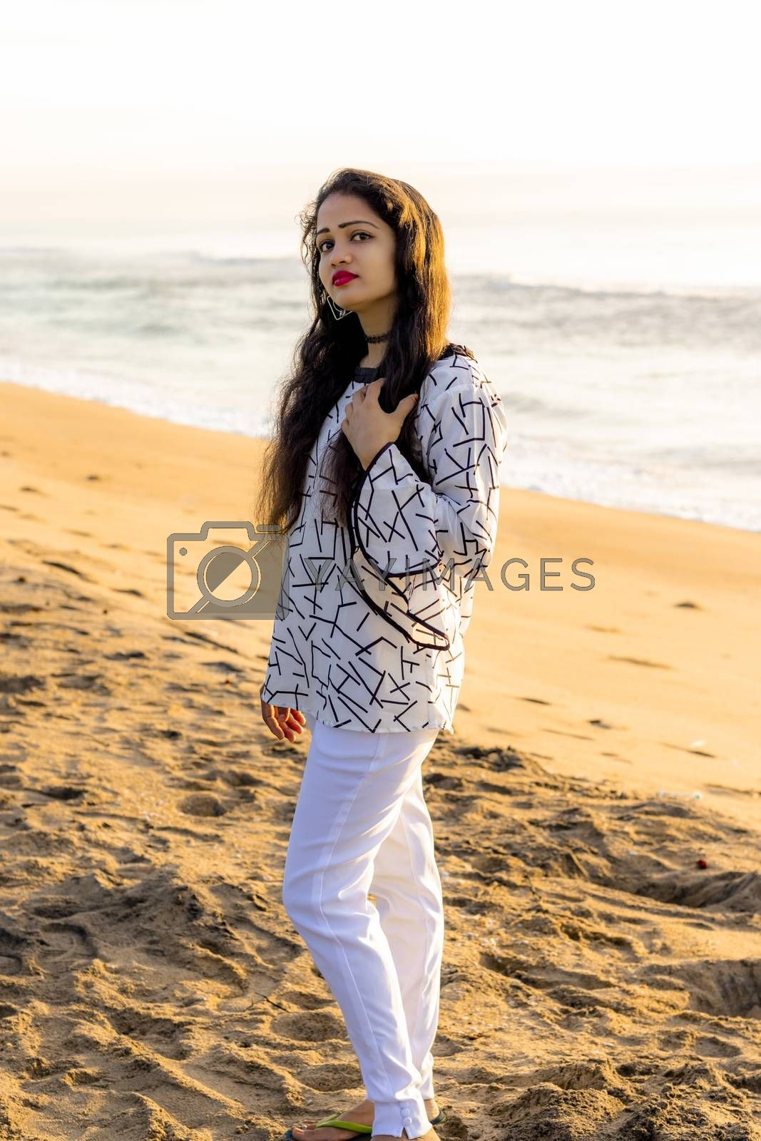A beautiful Asian model in white fancy fit tops and stylish cotton lycra stretchable trouser and blurred background of Indian beach bech