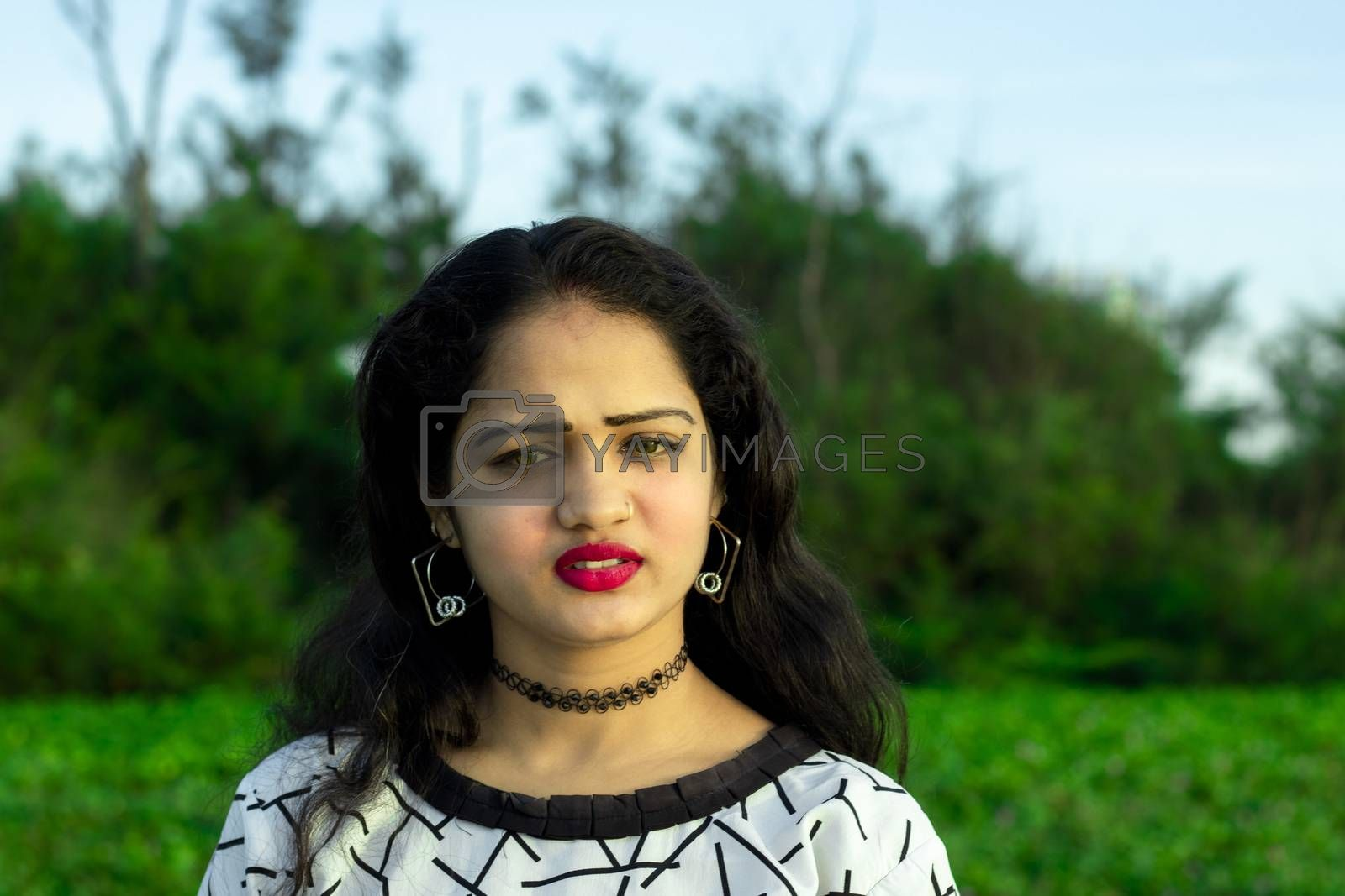 an indian model with closeup beautiful face and green blurred background of outside trees