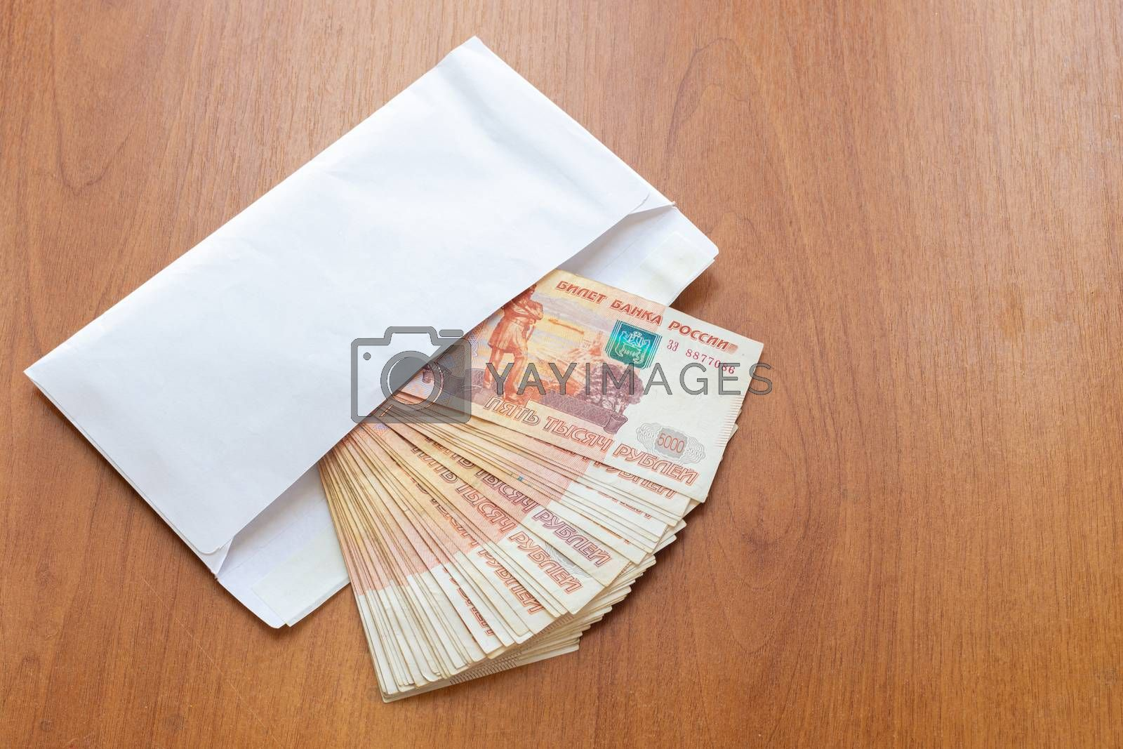There is a bundle of money in an envelope on the table