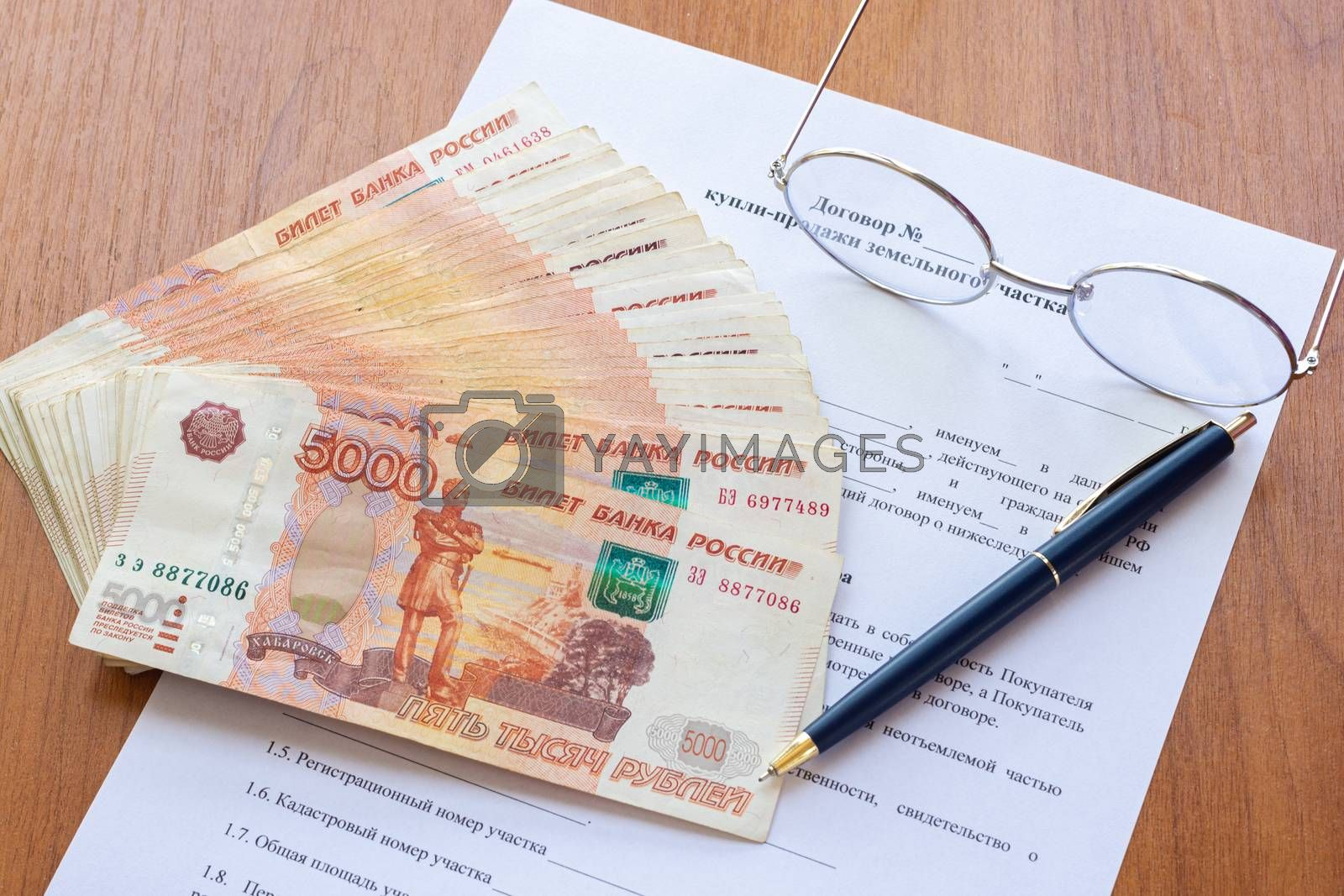On the table is a contract for the sale of a land plot, a bundle of money, a pen and glasses