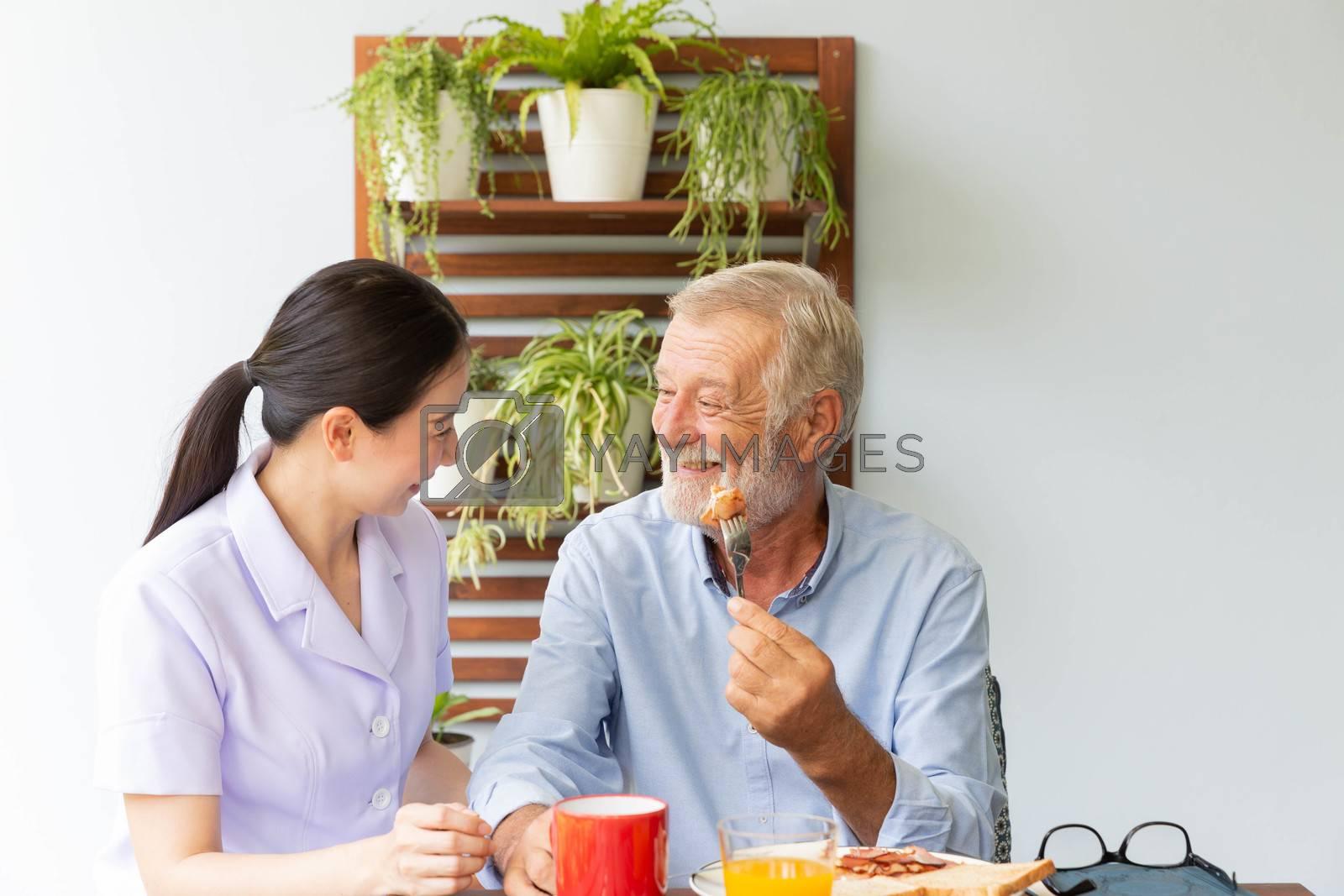 Asian nurse enjoy assist senior man having breakfast and happy together