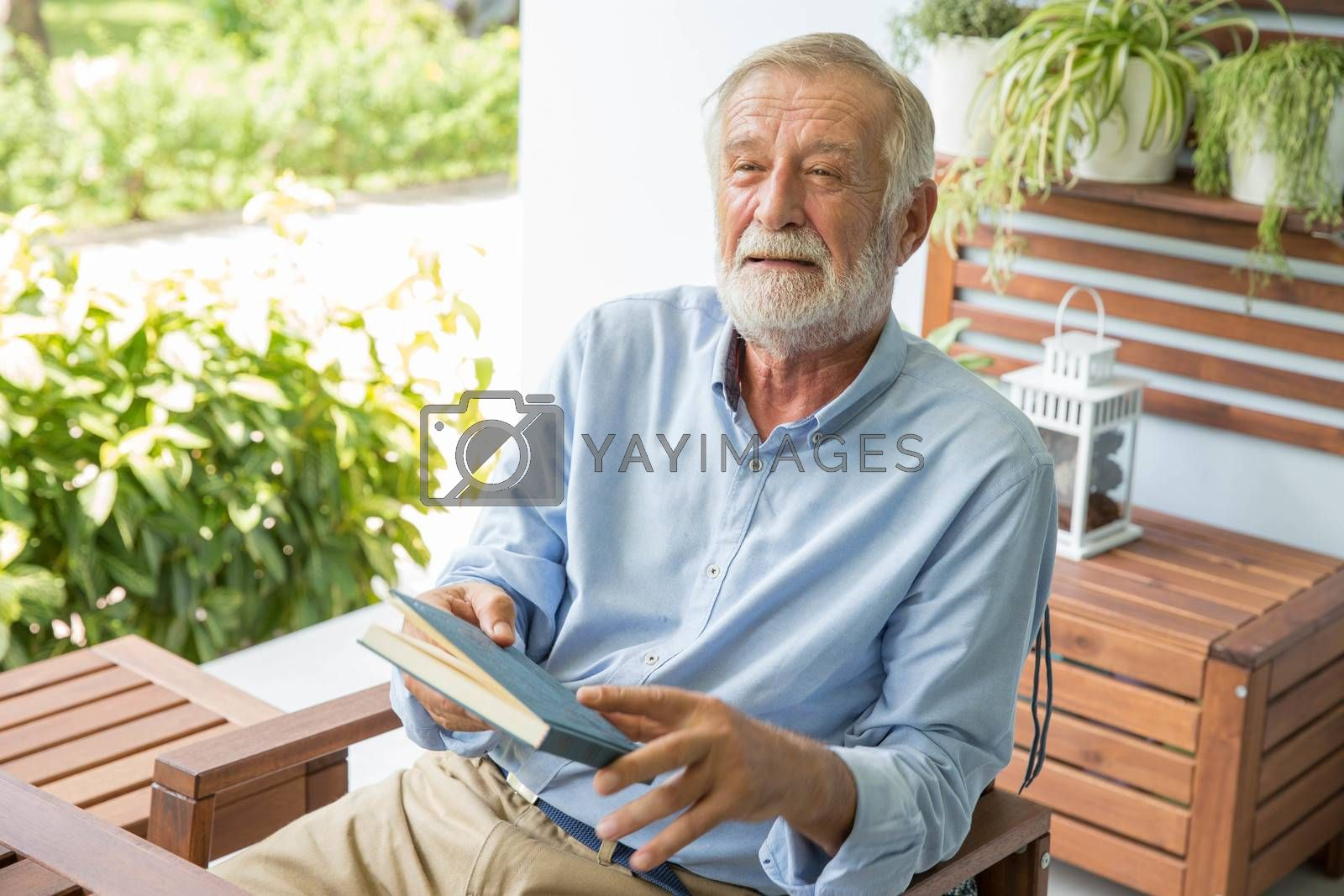 Senior retirement man happy reading book at home