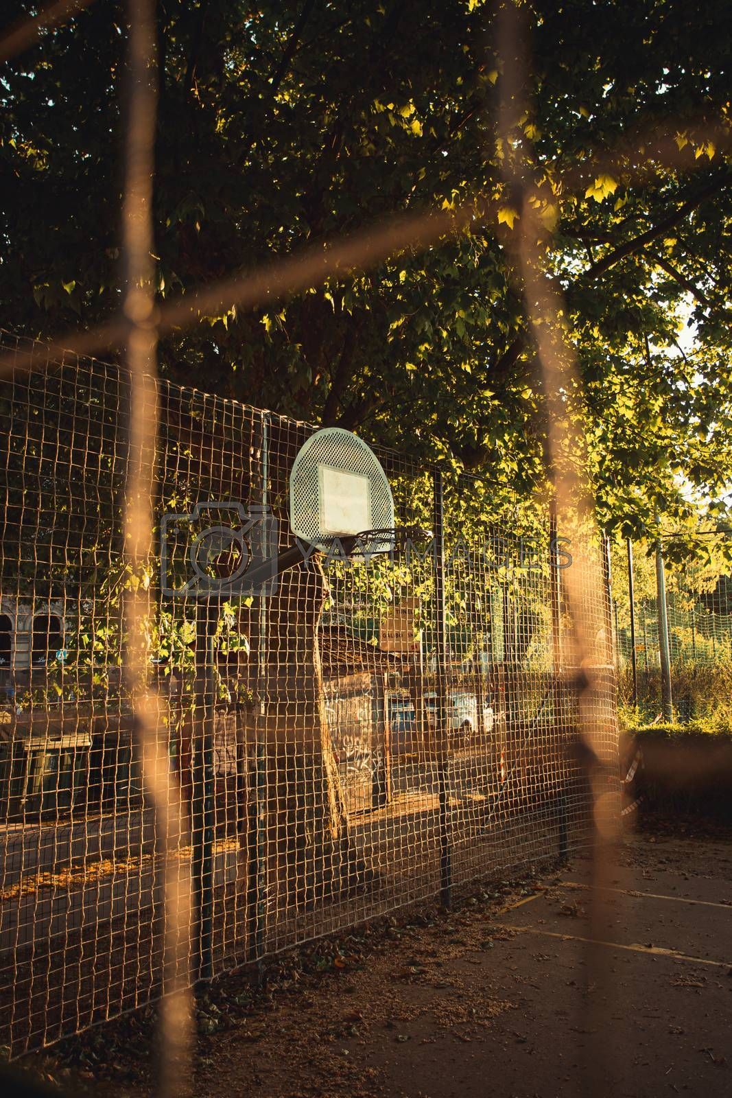 A close up of the basket from the fence in the court during a sunset