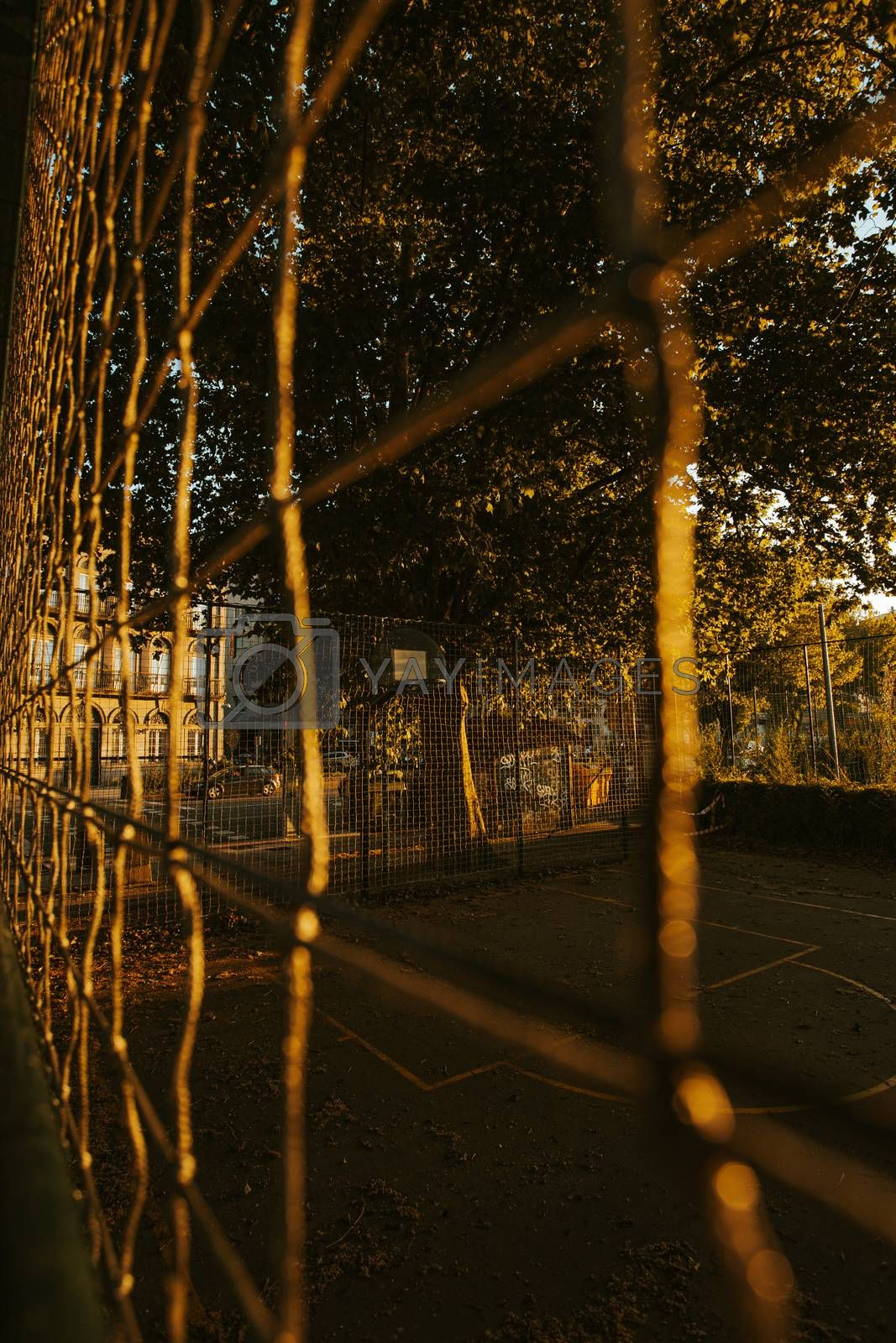 A close up of the basket court from the fence during a sunset