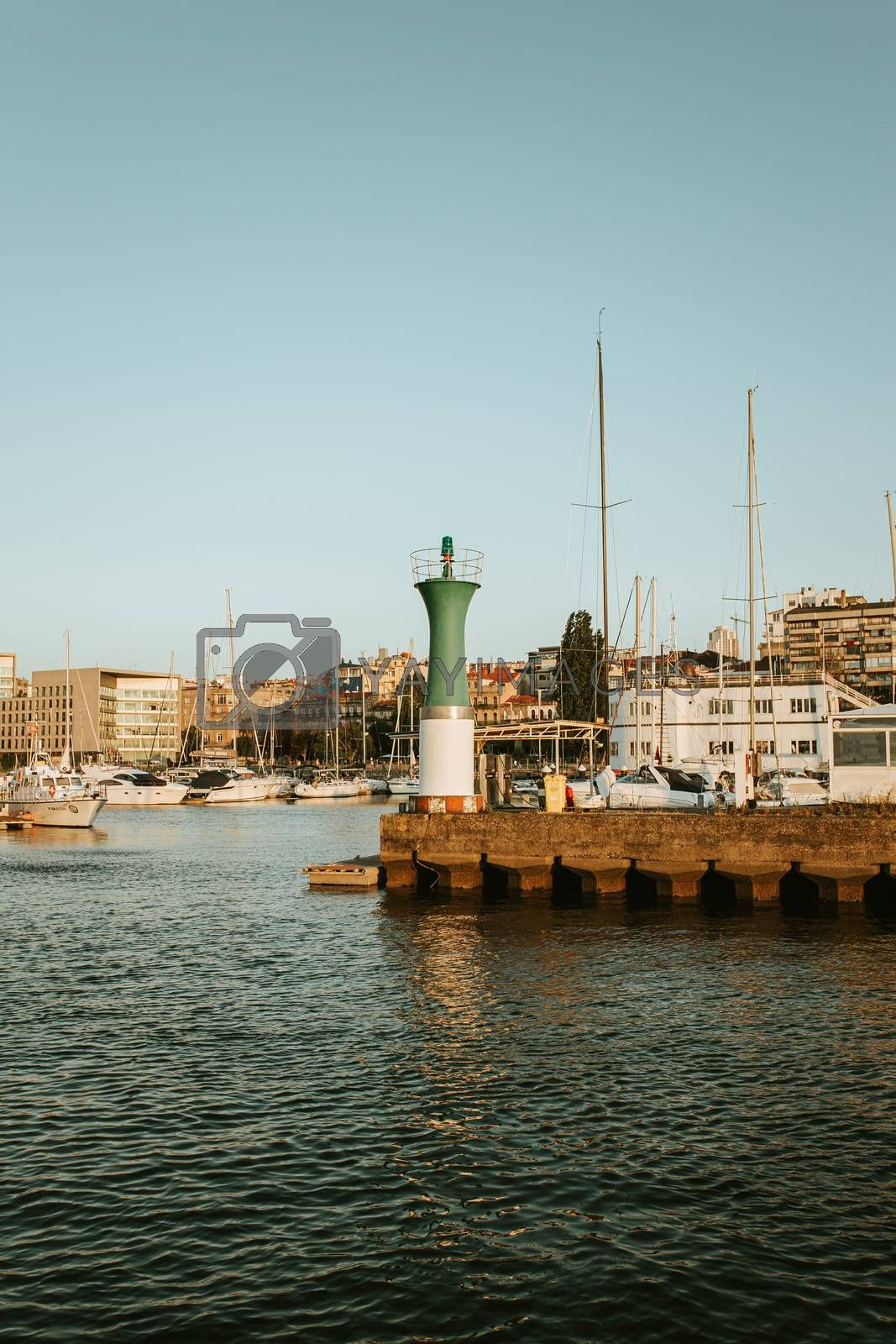 The green and white lighthouse in the sportive port of vigo during a sunny day