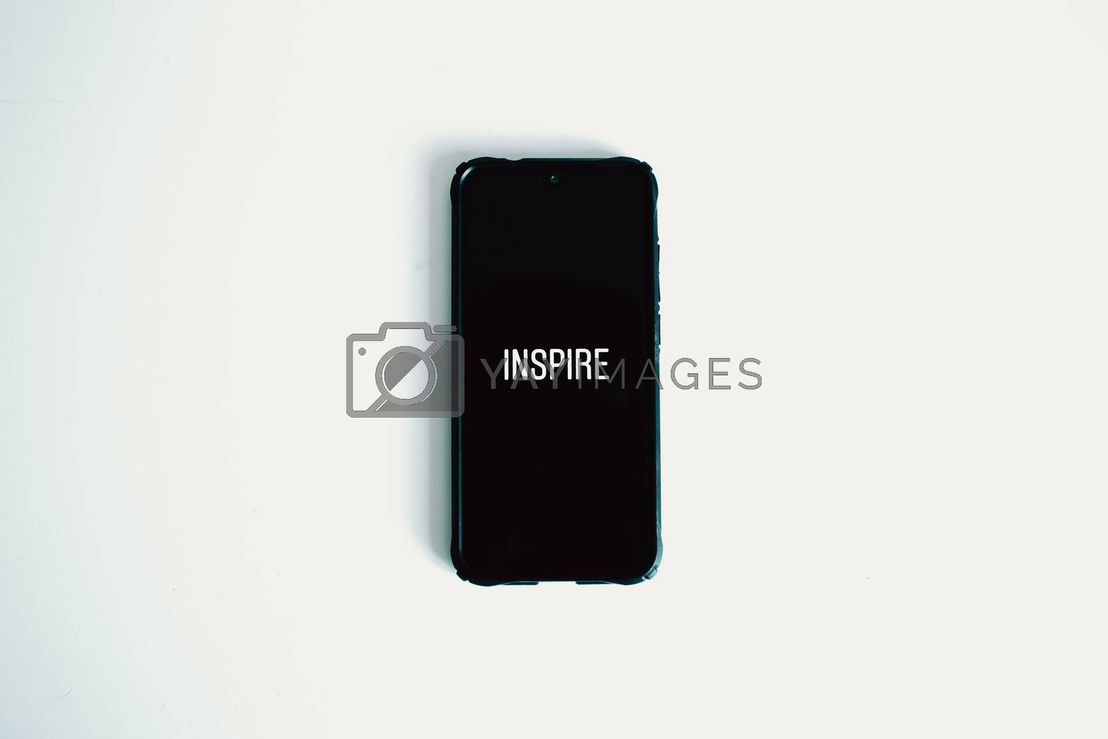 A flat lay of a black phone over a white background with the word inspire written in it