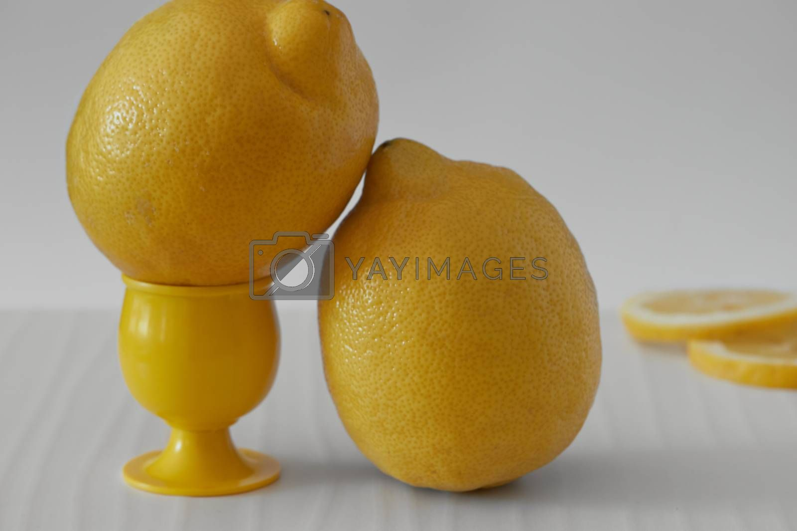 Several yellow sliced and whole lemons placed on a board with a light background