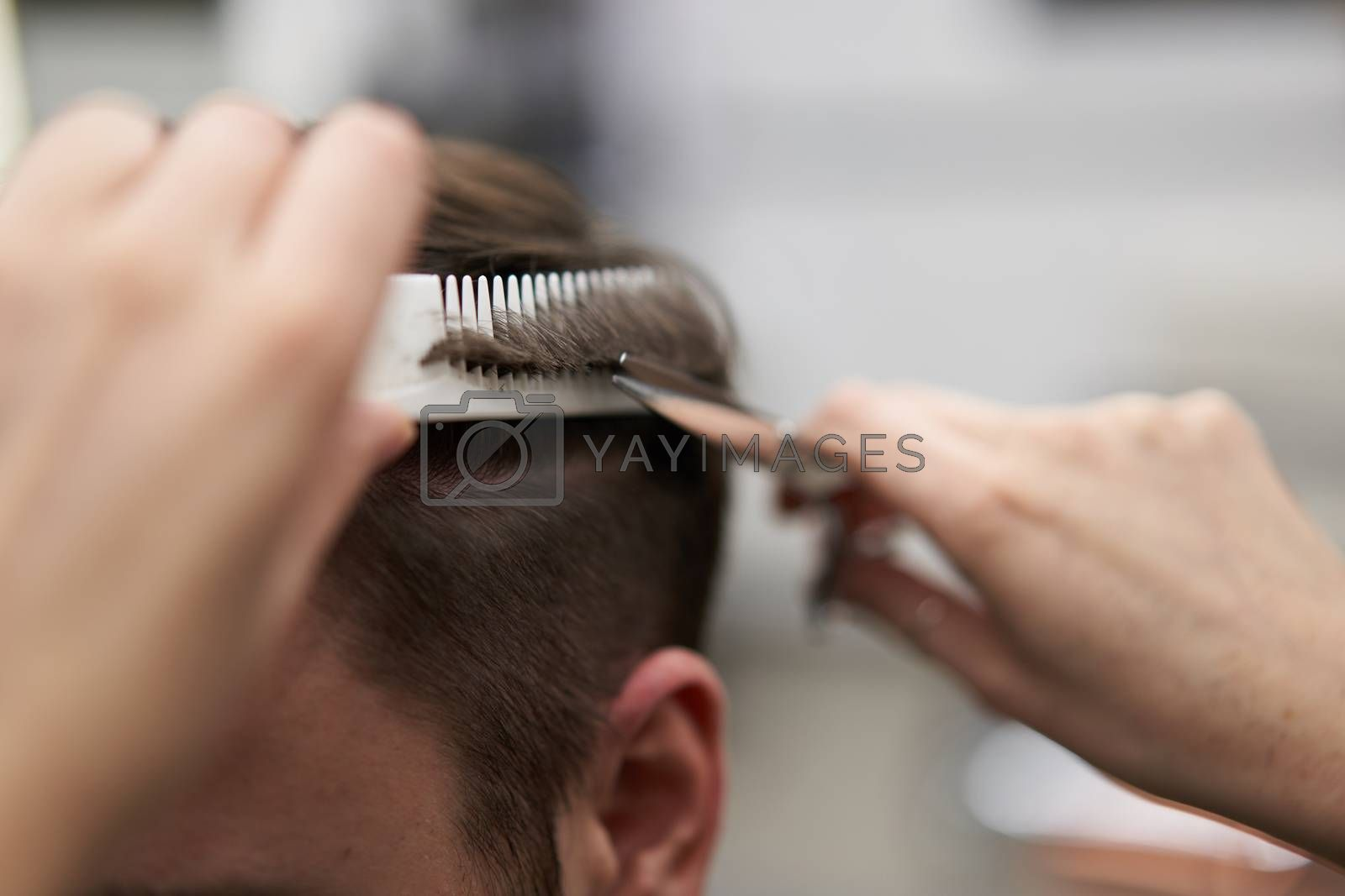 Beautiful caucasian woman hairdresser doing hairstyle to client. Close up portrait female barber with hairdressing tools at work. hair cutting process Hairstyling in modern barbershop. Professional