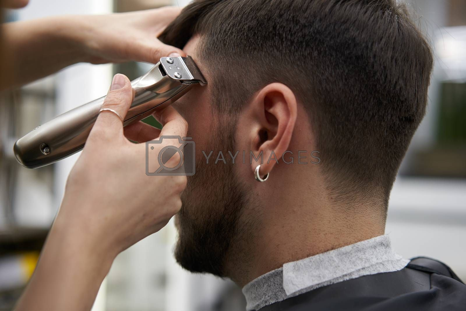 Beautiful caucasian woman hairdresser doing hairstyle to client. Close up portrait female barber with hairdressing tools trimmer at work. hair cutting process Hairstyling in modern barbershop.