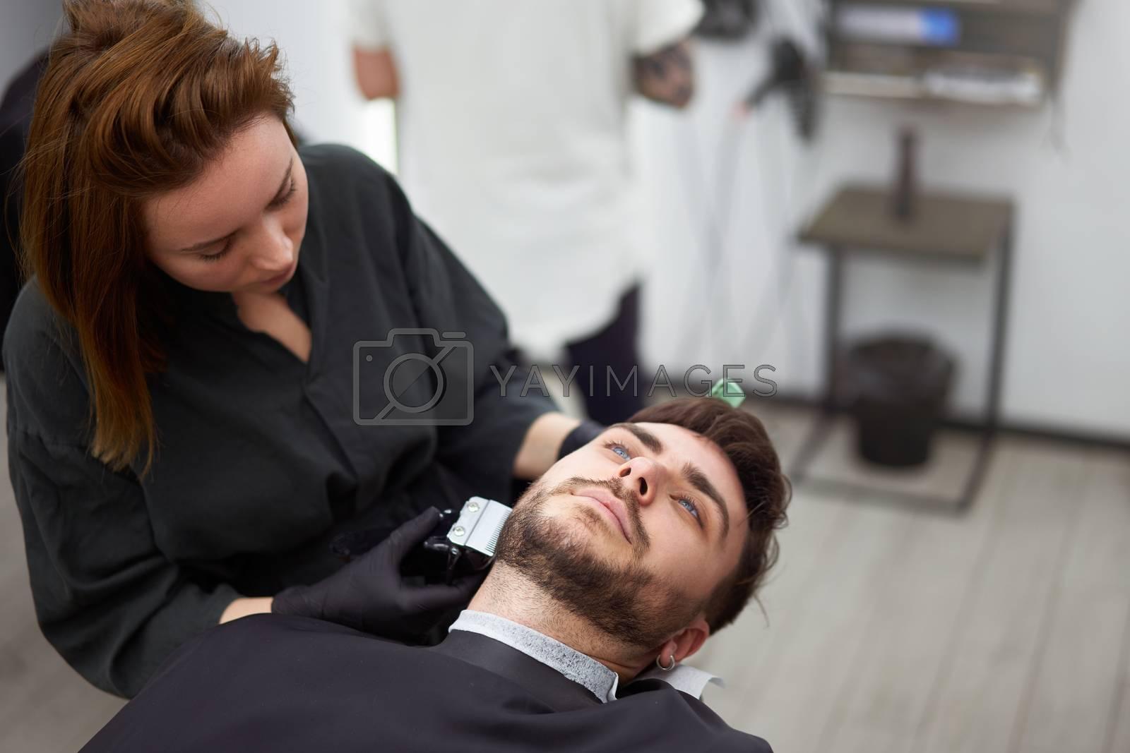 Young adult beautiful caucasian woman hairdresser cuts beard handsome man at modern barbershop Happy gay sitting chair men beauty salon. beard care. metrosexual. Female barber in black gloves serving
