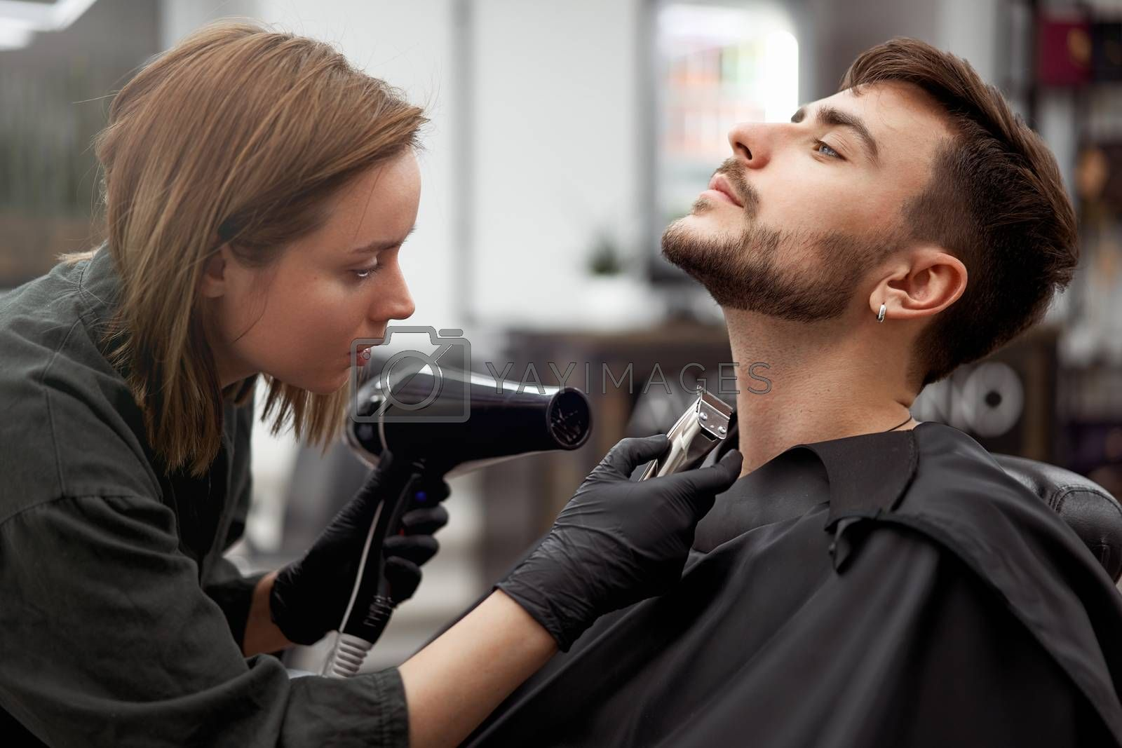 Stylish man sitting barber shop Hairstylist Hairdresser Woman blow dry his hair Portrait handsome happy young bearded caucasian guy getting trendy haircut Attractive barber girl serving client