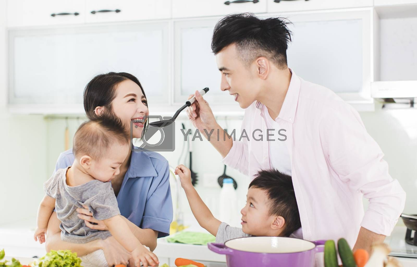 happy family tasting the soup in kitchen