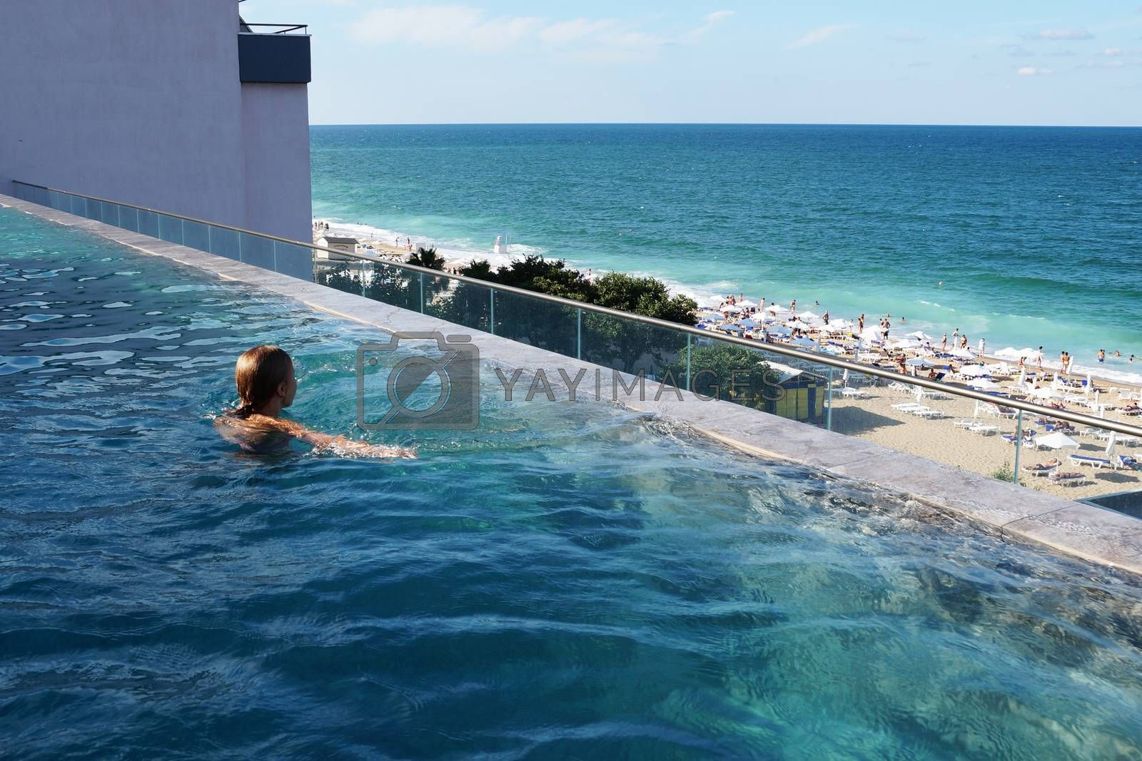 teenage girl swimming in the rooftop pool with sea view.