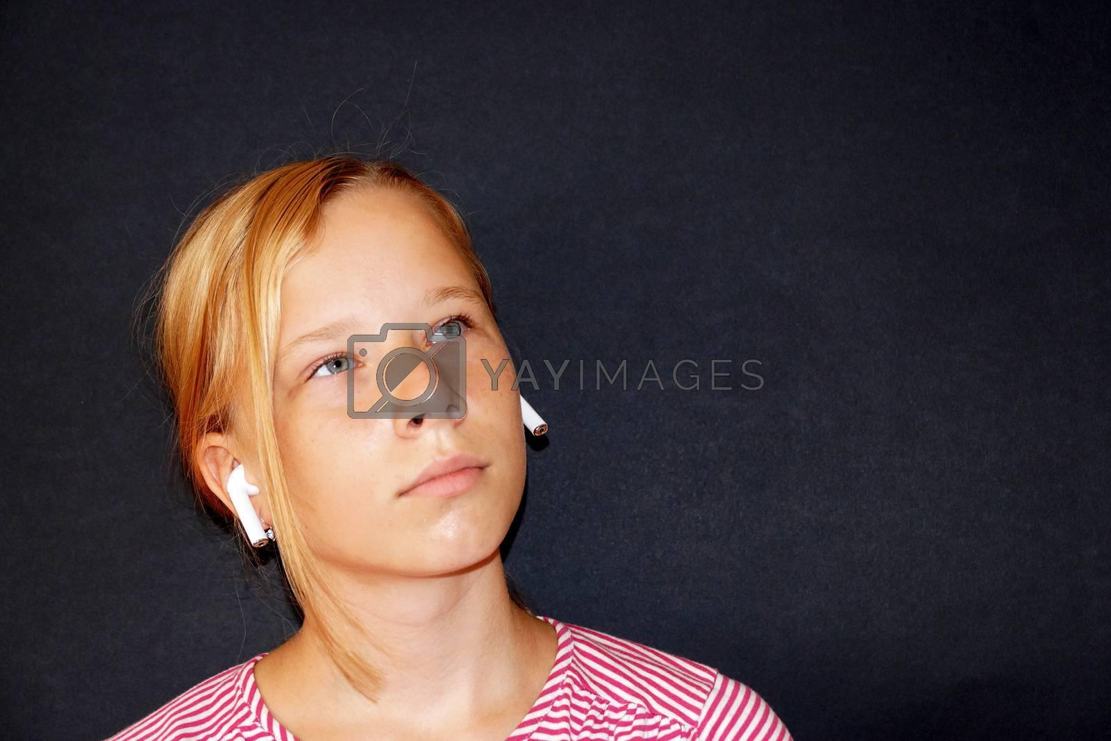 teenage girl listening to music on headphones , portrait on black background.