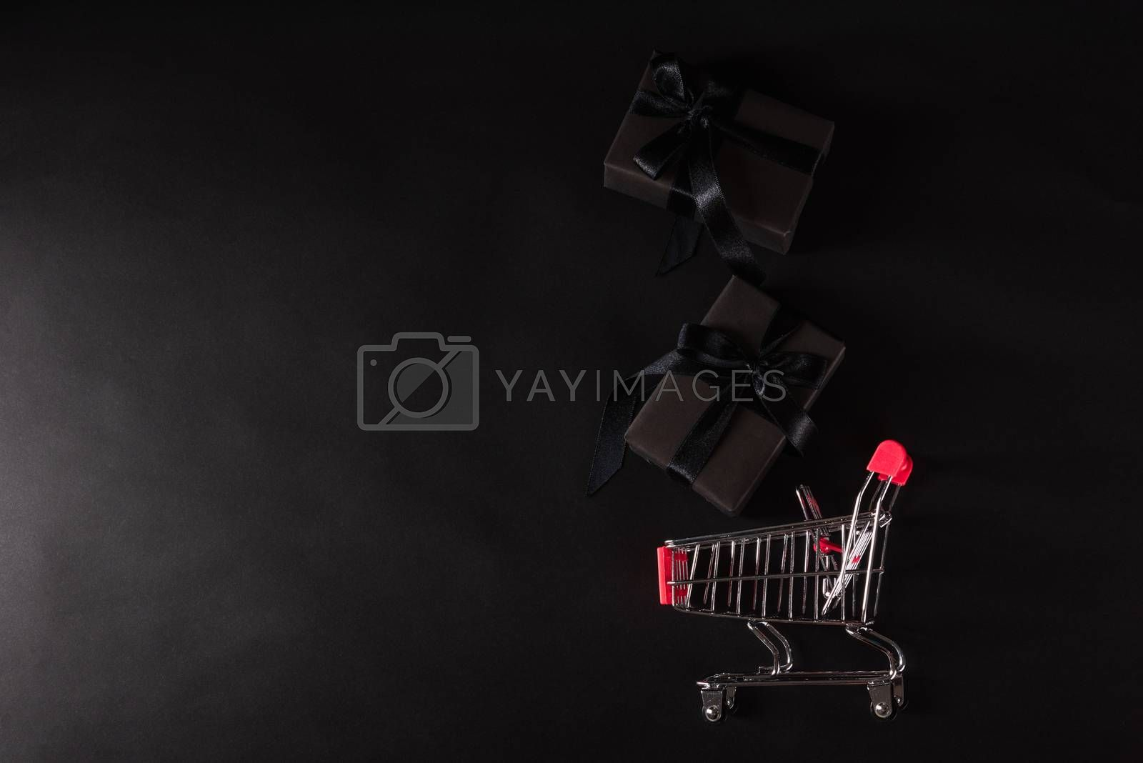 Black Friday sale shopping concept, Top view of gift box wrapped black paper and black bow ribbon present dropping to the shopping cart, studio shot on black background