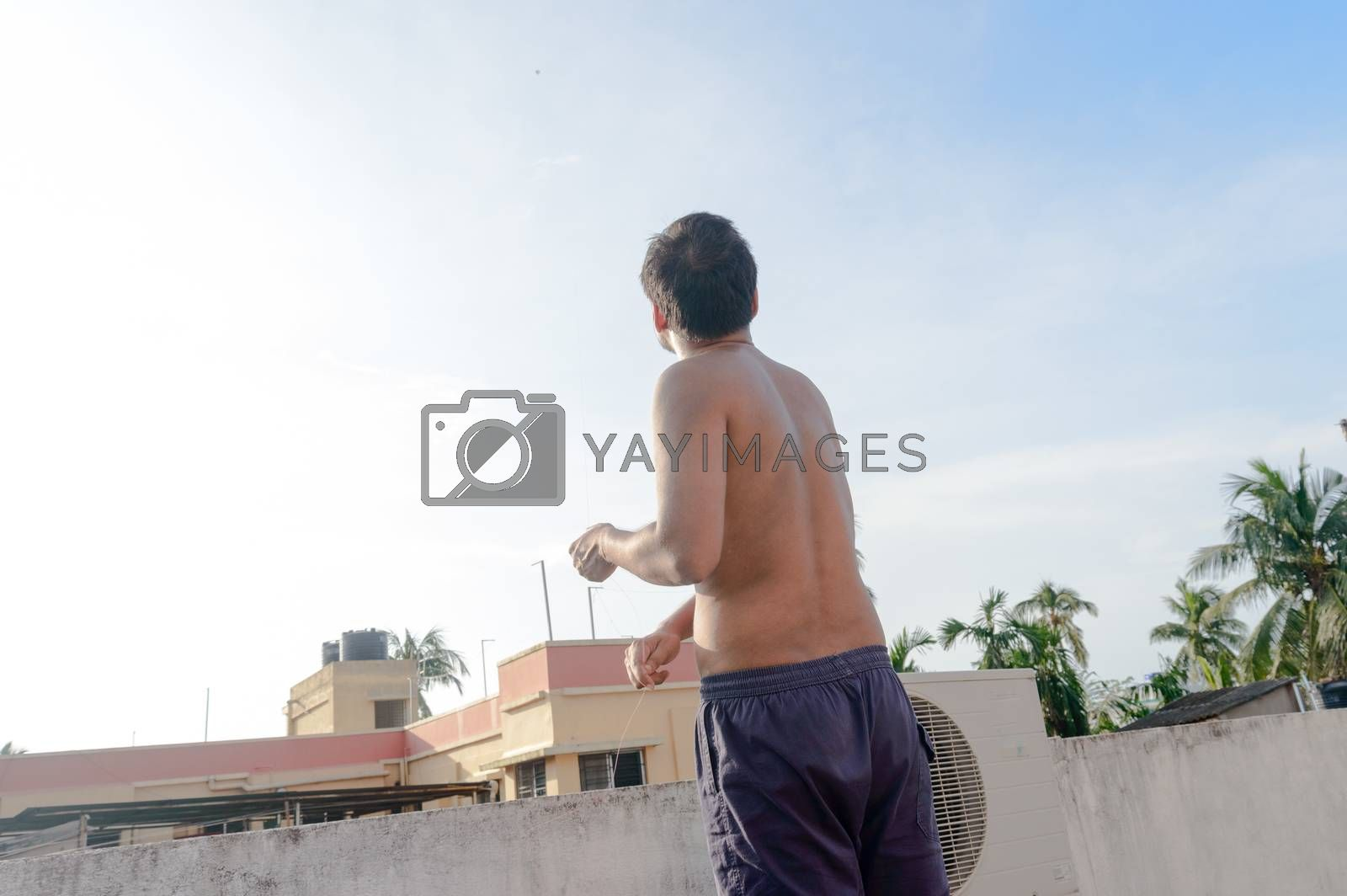 A man flying Kite in the sky. Kites flying picture with blue sky and white clouds. Photography in the eve of Vishwakarma Puja in Kolkata.