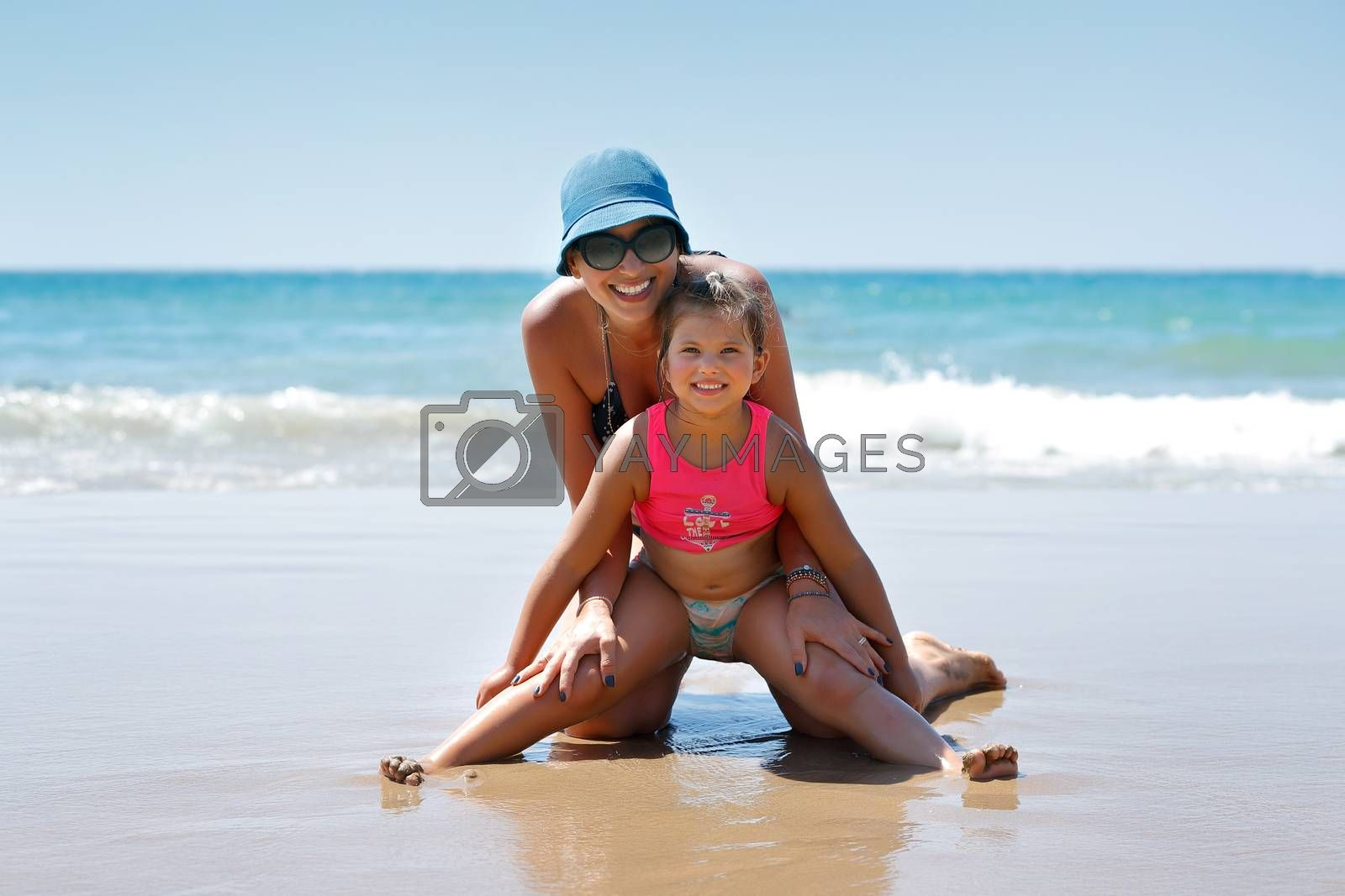 Joyful Mother and Daughter Playing on the Beach. Enjoying Summer Vacation on the Beach Resort. Leisure Time Together. Happy Family Time.