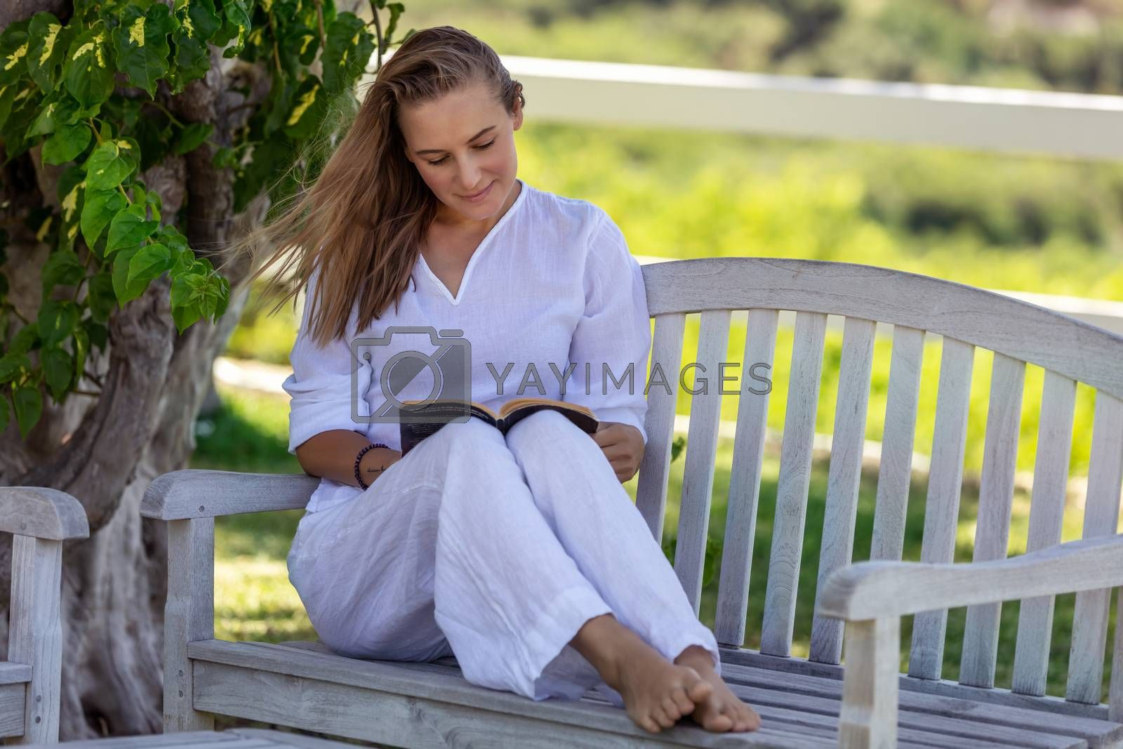 Beautiful Young Woman Sitting on the Bench in the Park and Reading Book. Spending Nice Summer Day with Good Story. Peace and Relaxation Concept.