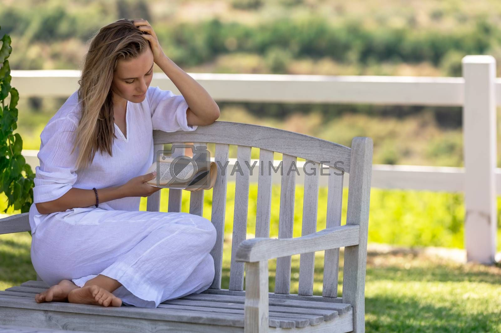 Beautiful Young Woman Sitting on the Bench in the Park and Reading a Book. Spending Nice Summer Day with Good Story. Peace and Relaxation Concept.