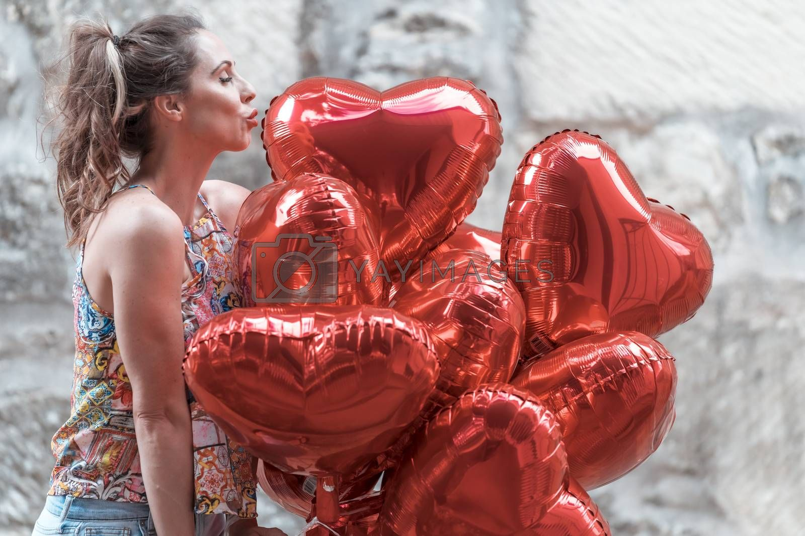 A beautiful brunette model with a dozen balloons for Valentines Day