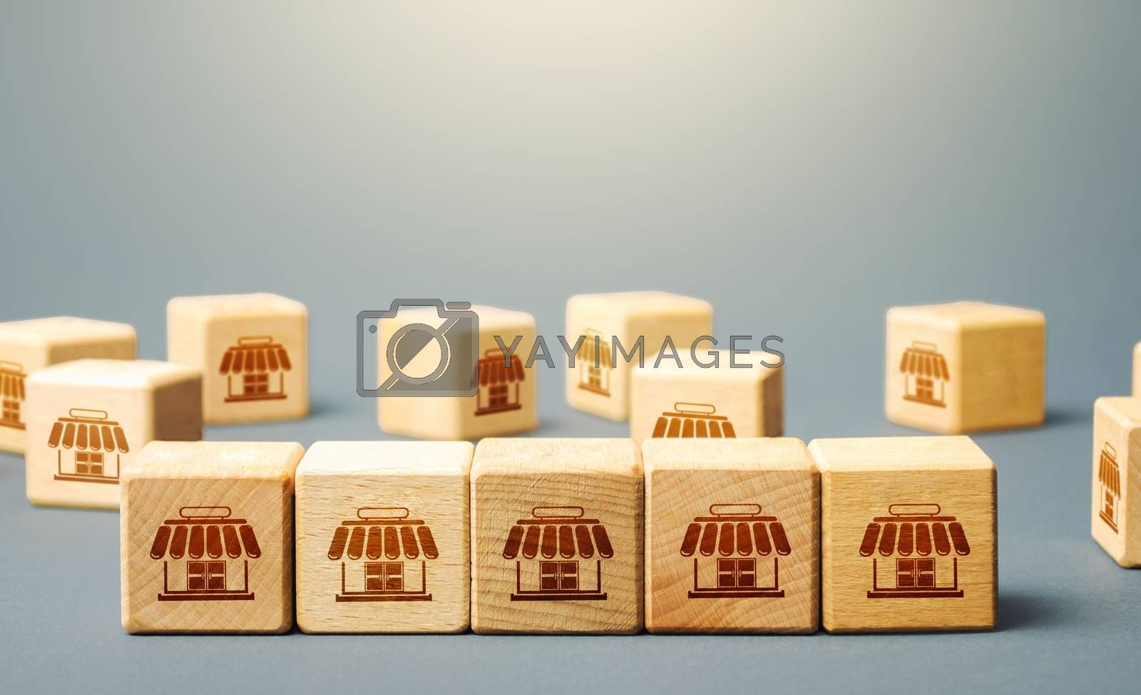 Blocks symbolizing shopping stores. Building a successful business empire. Franchise concept. Merging competitor, creation of a large network monopoly. Commercial association