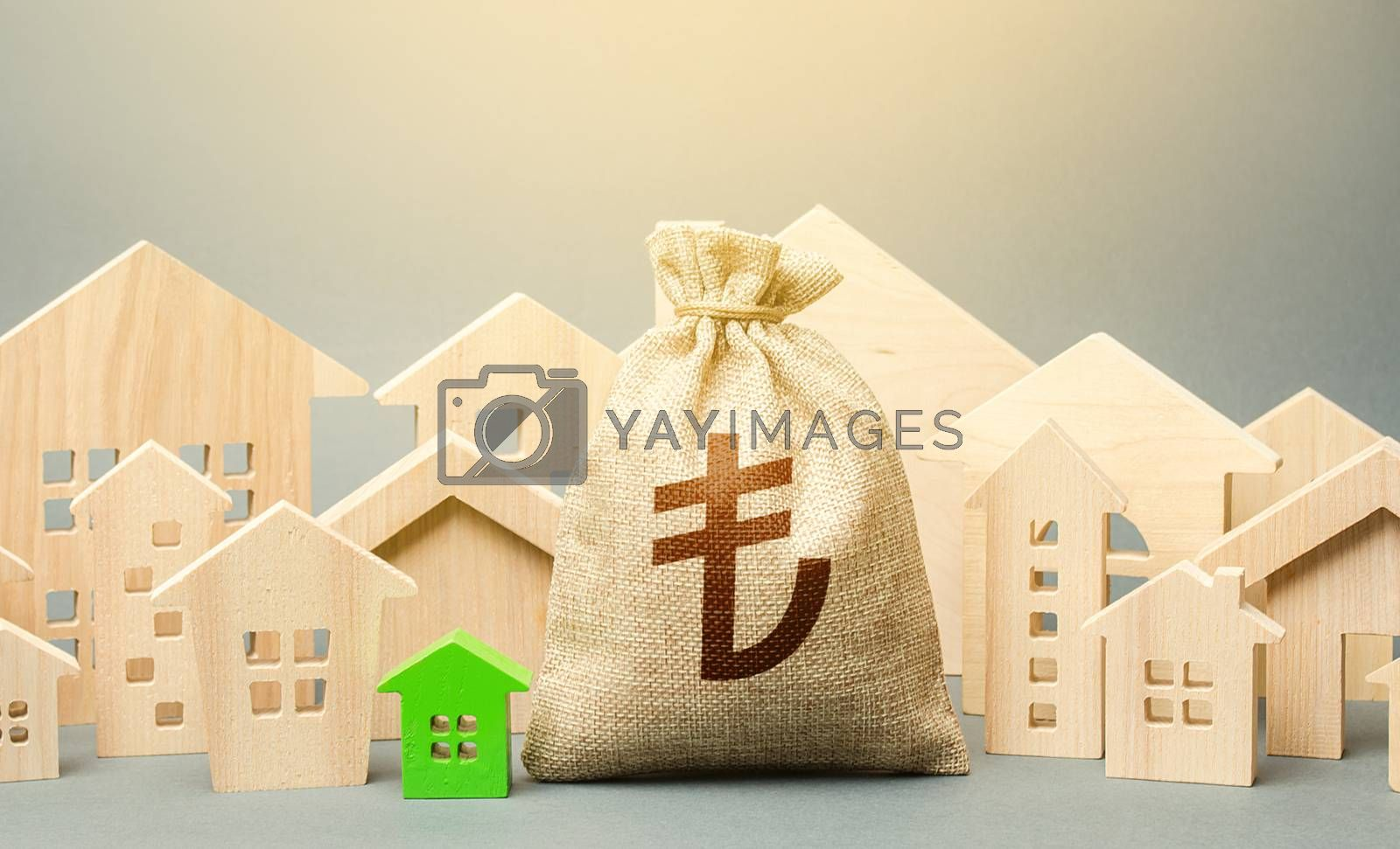 Turkish lira money bag and a city of house figures. Investments. City municipal budget. Buying real estate, fair price. Cost of living. Property tax. Development, renovation of buildings.