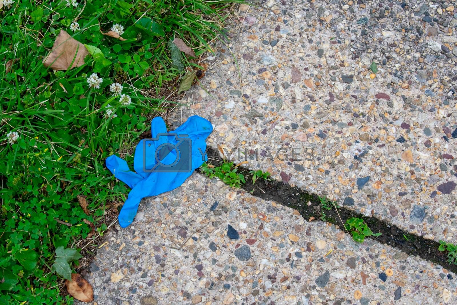An Old Blue Medical Glove on the Sidewalk for Protection Against COVID-19