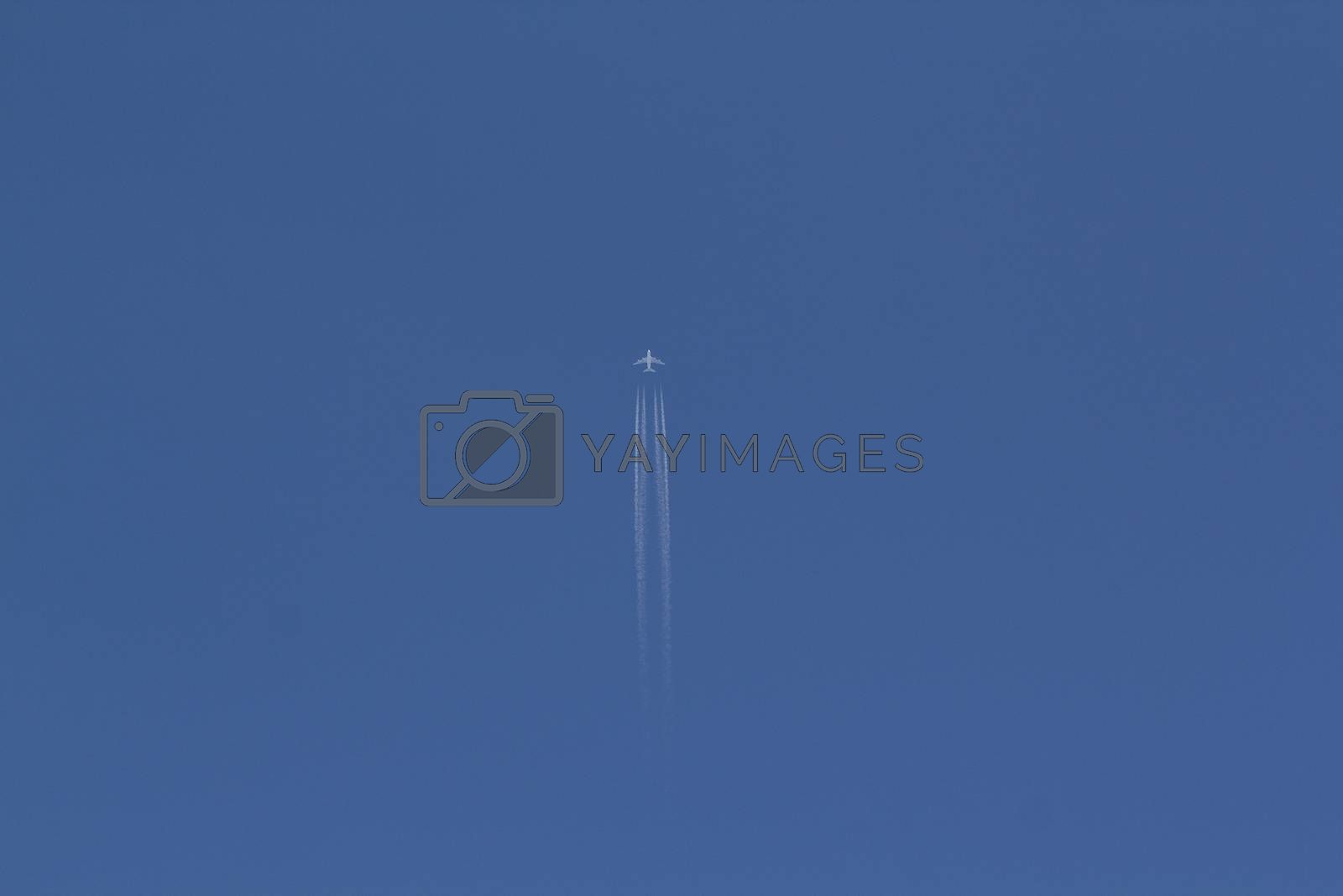 A jet plane leaving a white vapour trail in a clear blue sky